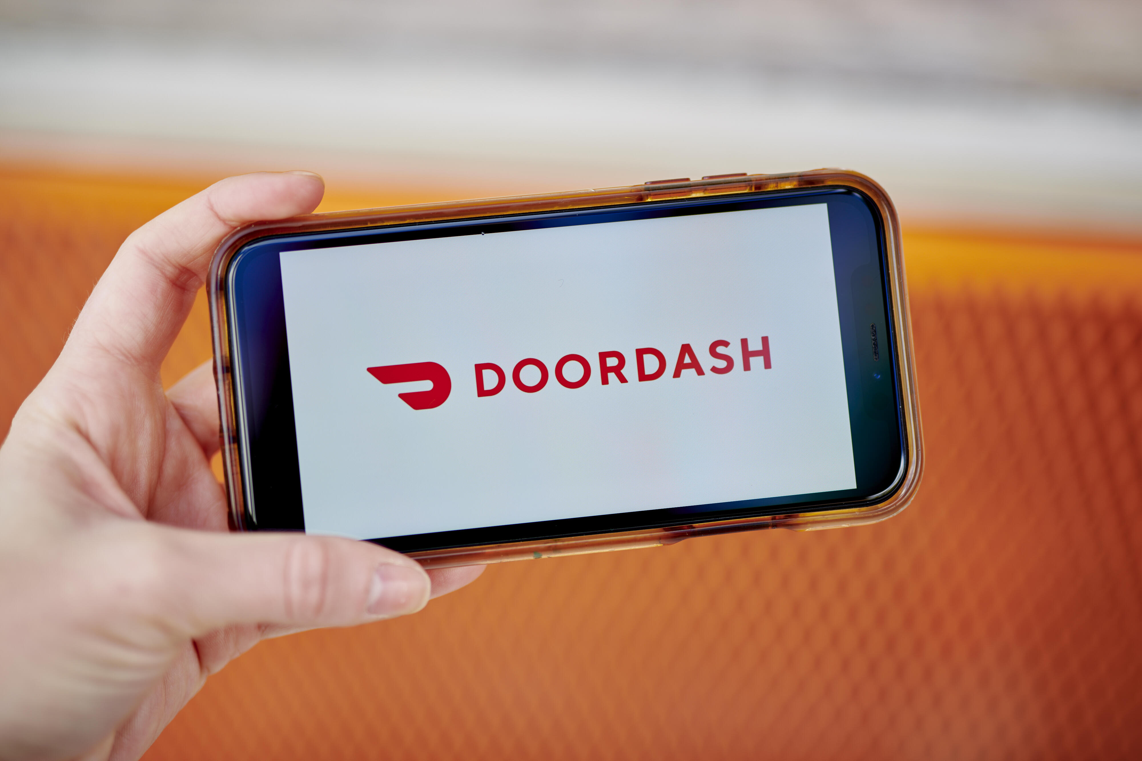 In this photo illustration the DoorDash logo is seen