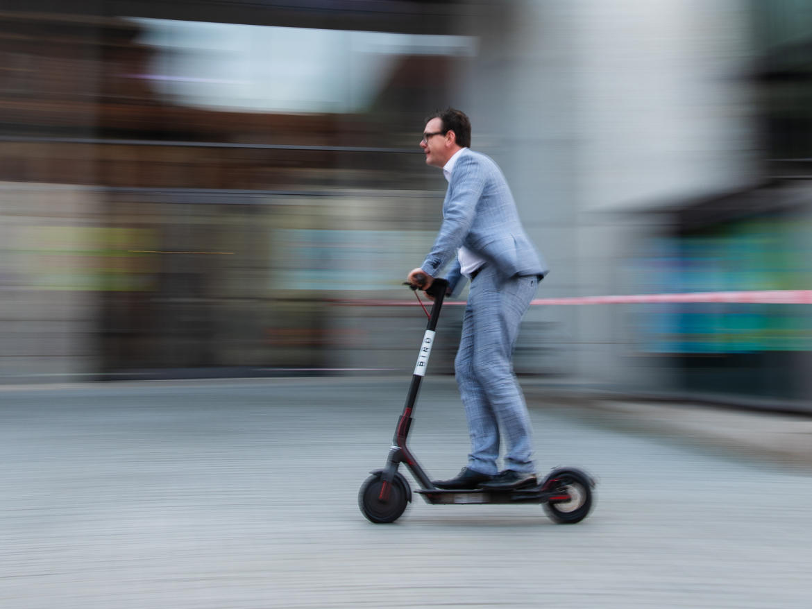A man zips along on an e-scooter, in front of a motion-blur background