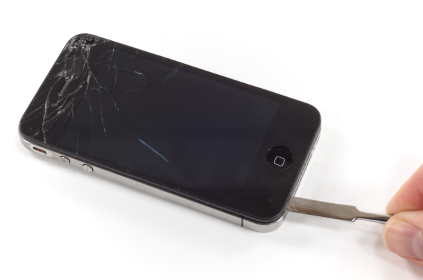 An iPhone 4 with a cracked screen being repaired.