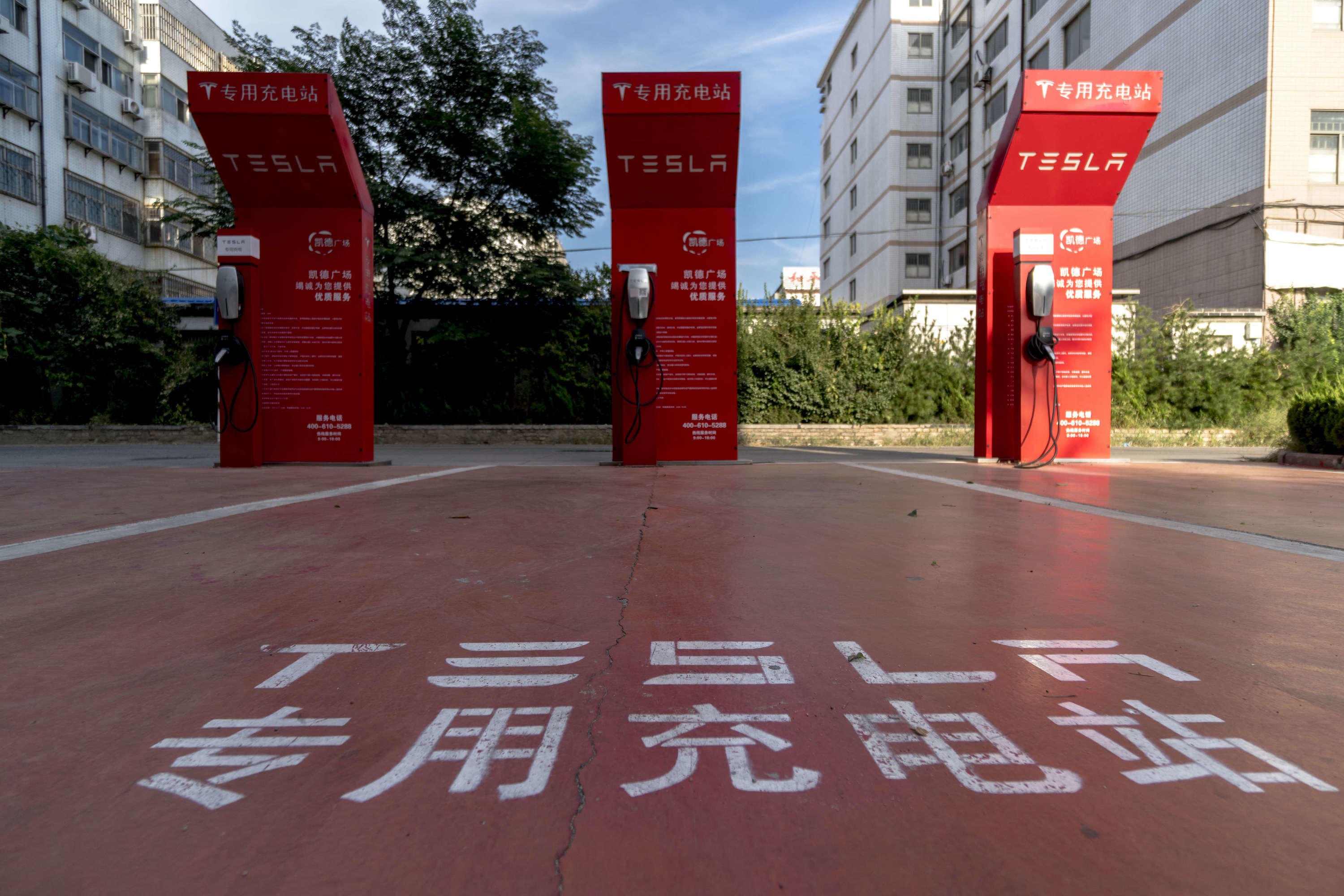 A vacant Tesla charging station on a parking lot beside a
