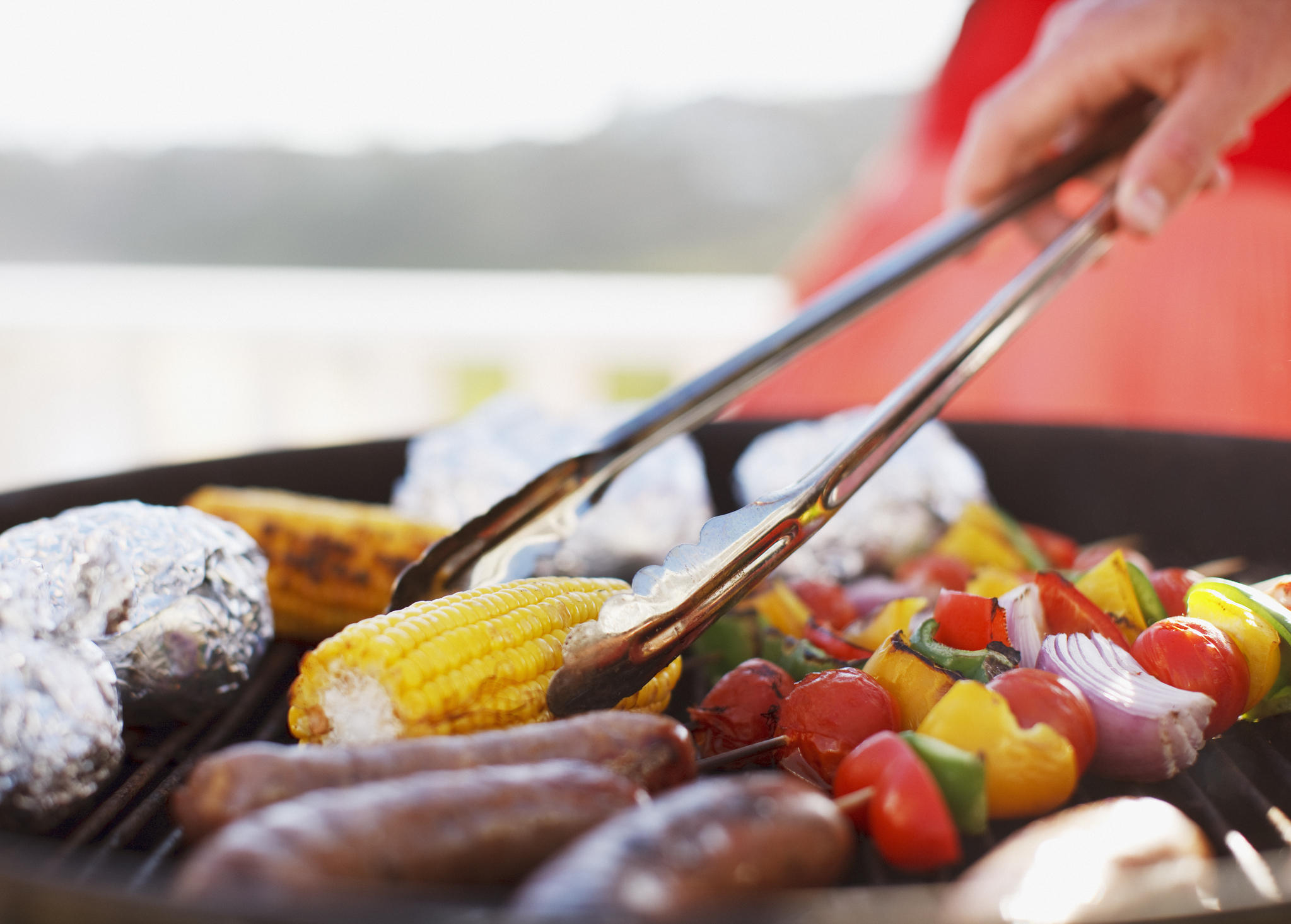 <p>Close up of man grilling food on barbecue</p>