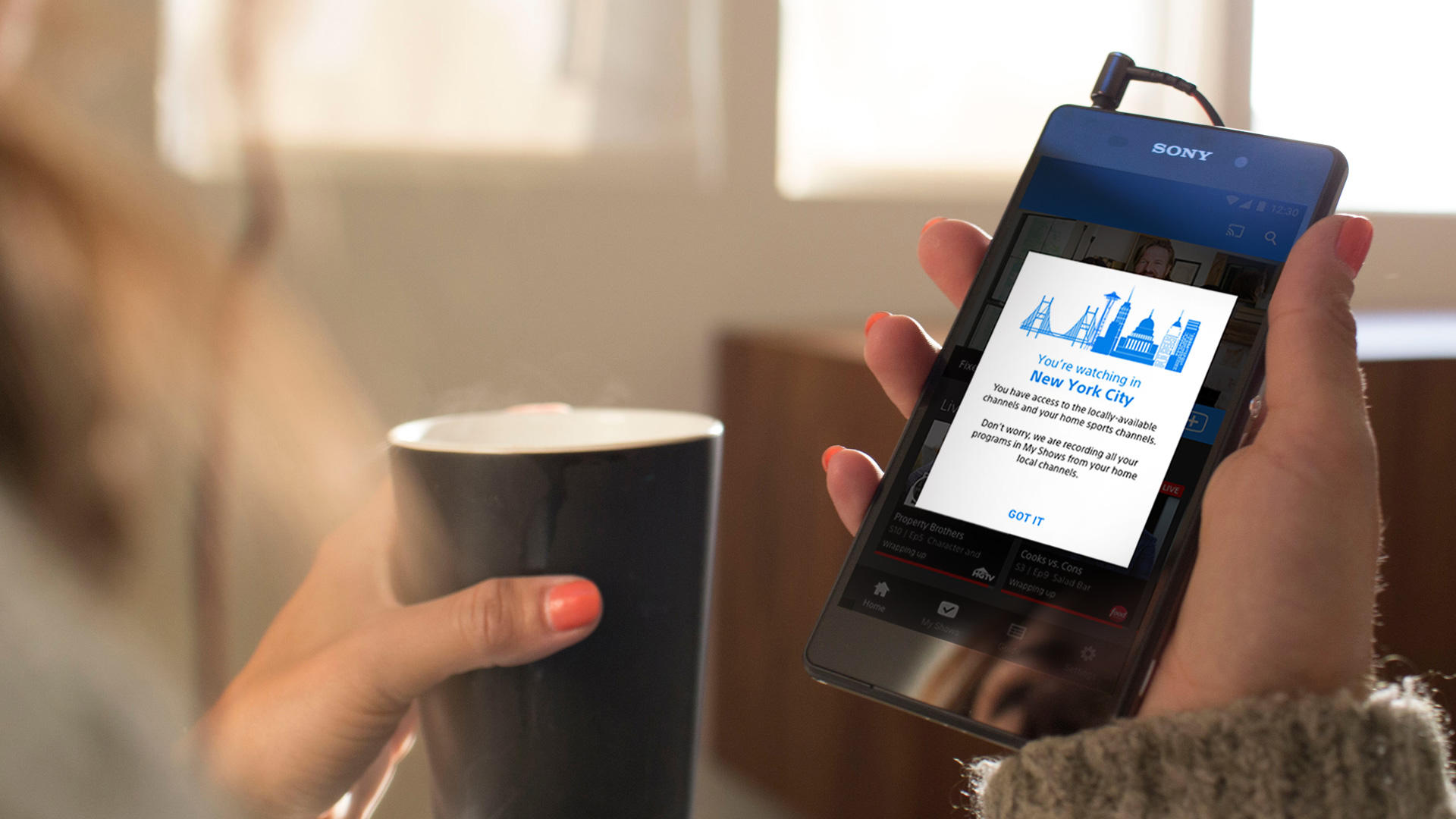 A woman holds a phone to sign up for Playstation Vue