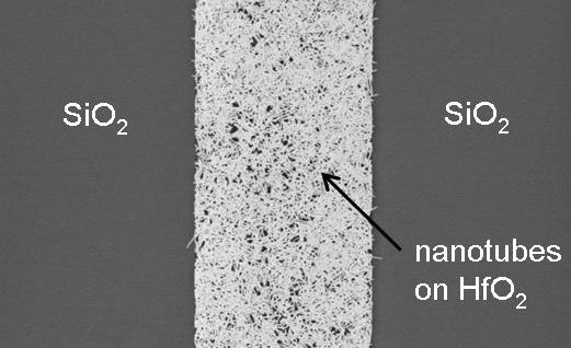 IBM's silicon wafers have two surfaces on top, hafnium oxide and silicon dioxide. This close-up image shows speckles of carbon nanotubes that bond only with the hafnium oxide, part of IBM's approach to positioning them precisely on a chip.