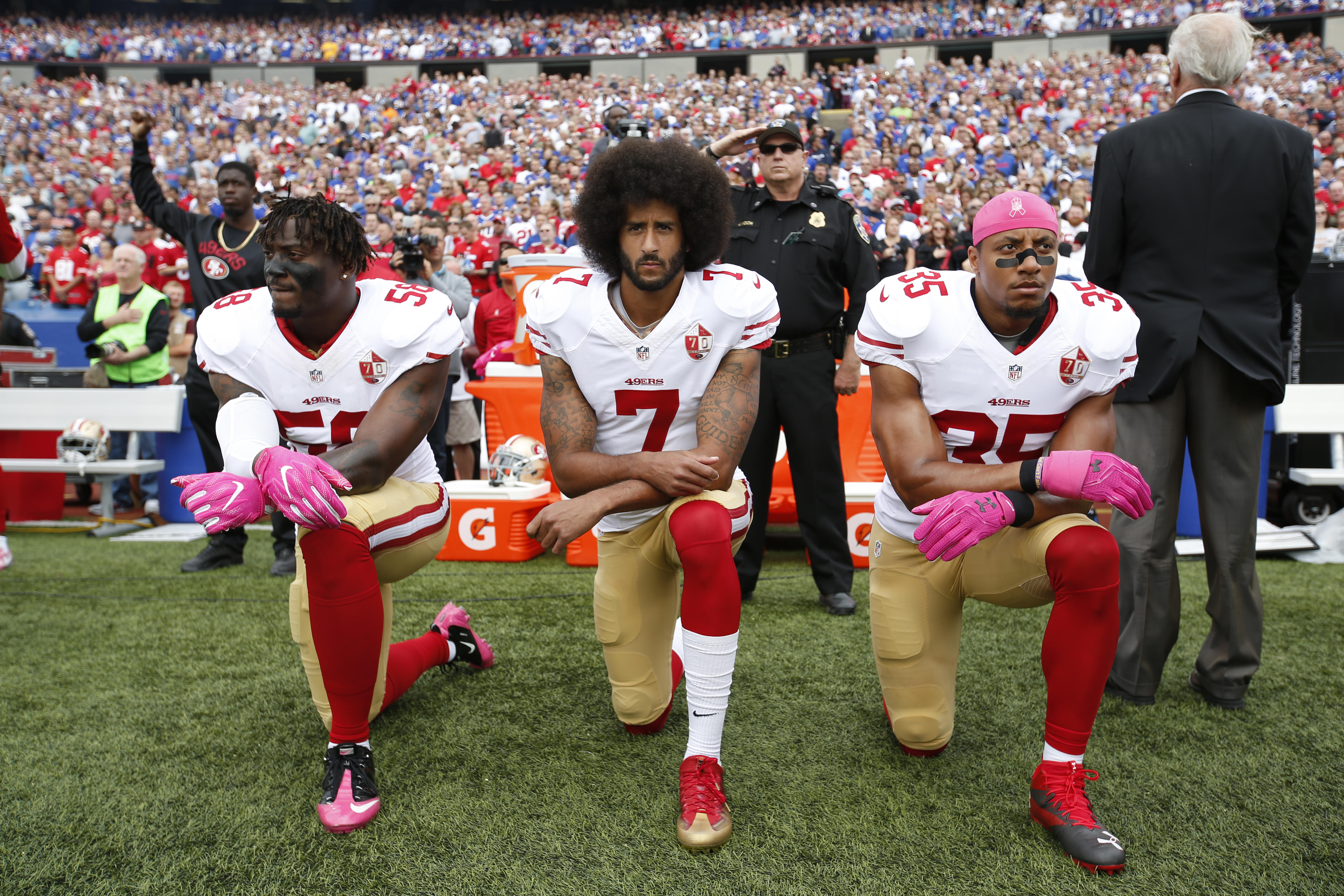 Colin Kaepernick (center) said his original protests during the national anthem, like this one before a game in October 2016, were meant to draw attention to police misconduct.