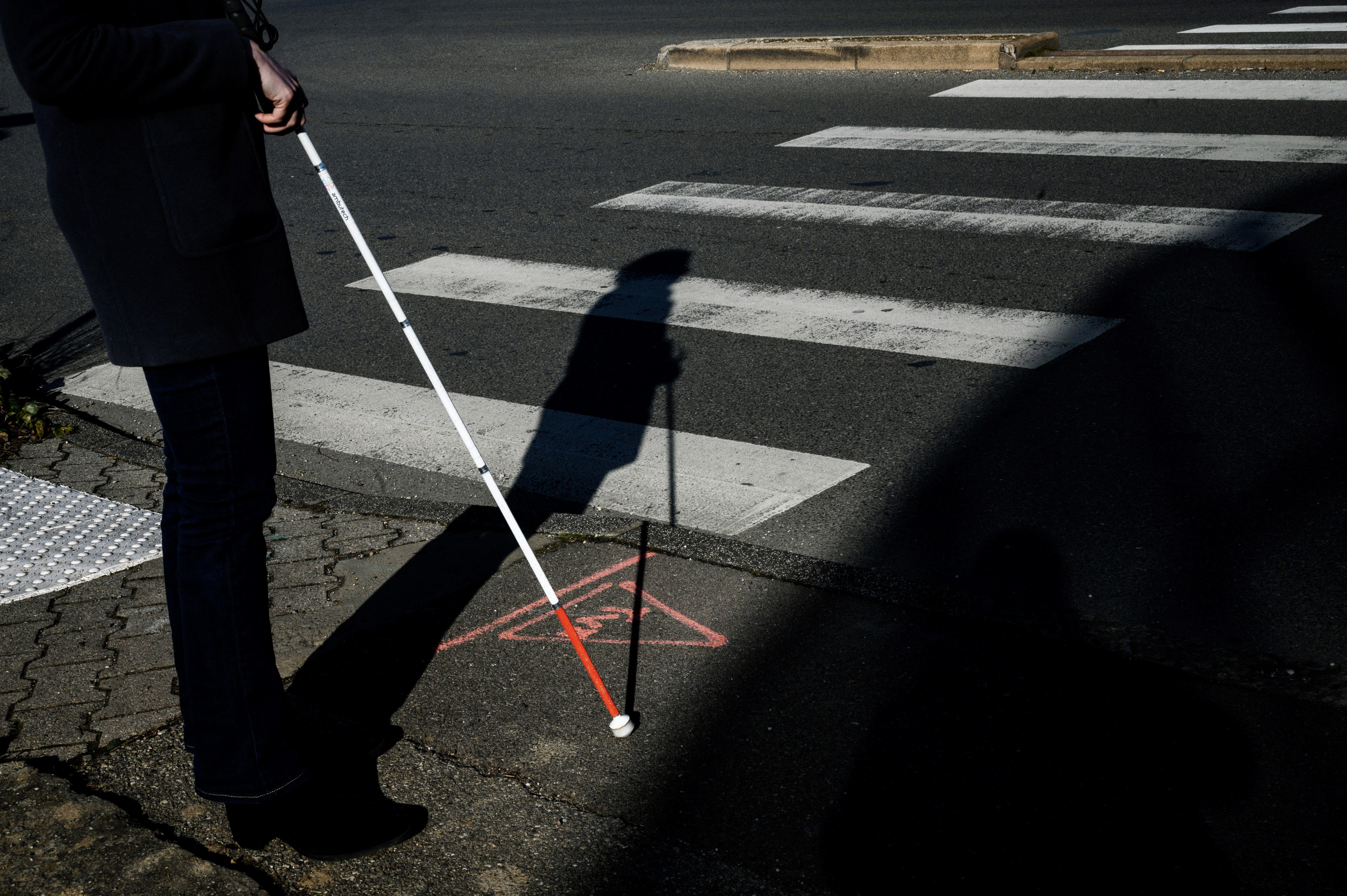 Photo of a visually impaired person with a cane, standing next to a crosswalk.