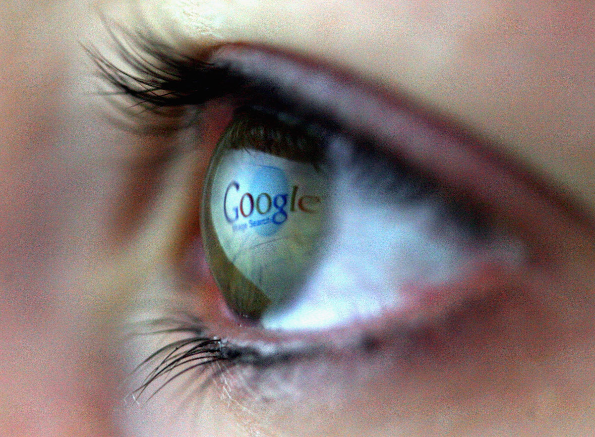 Google logo reflected in a human eye.