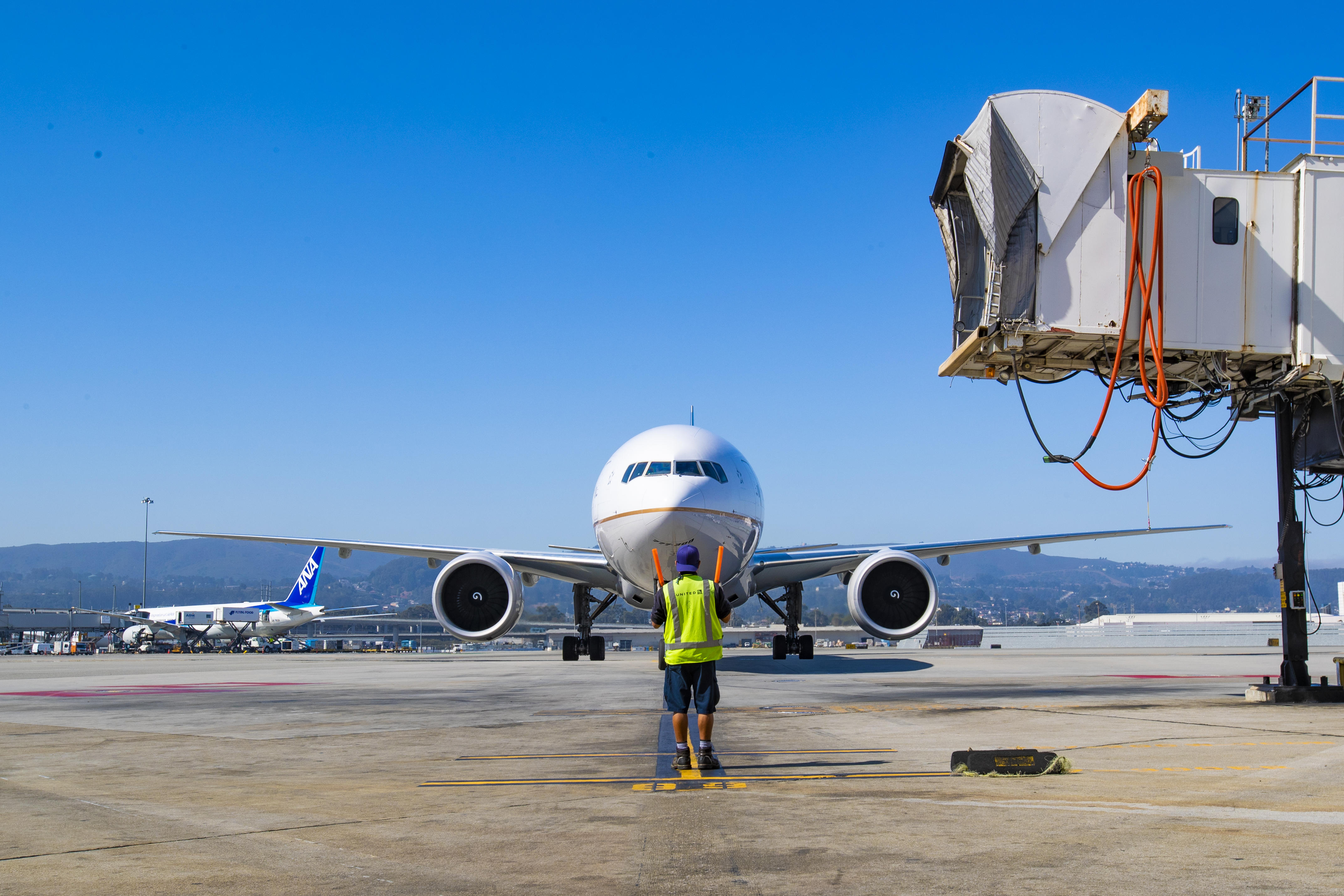 A ground crew member guides a United Airlines Boeing 777 to its gate.