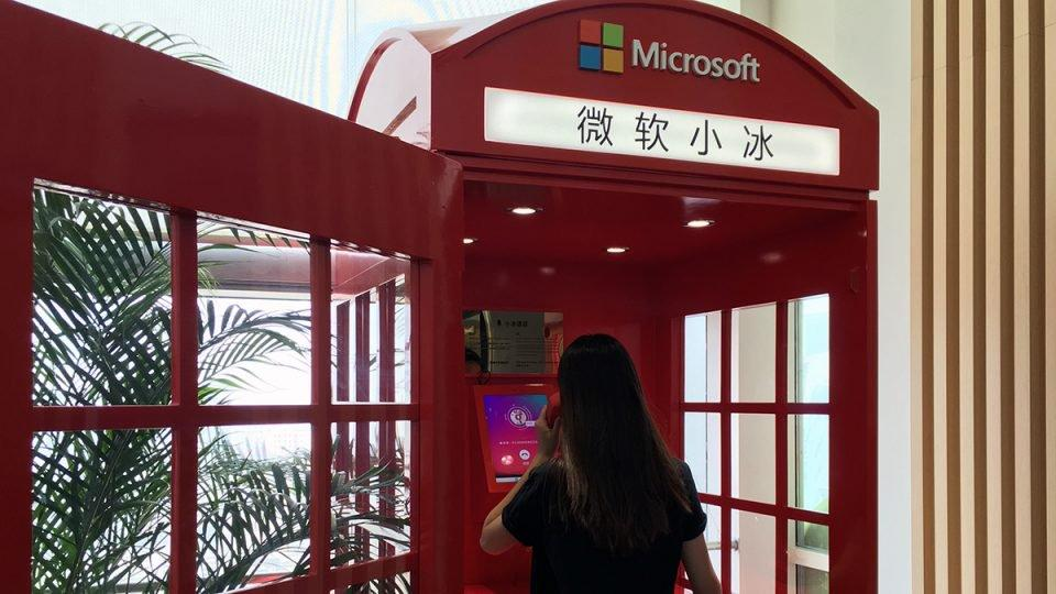 A woman makes a call in a Microsoft-branded phone booth.