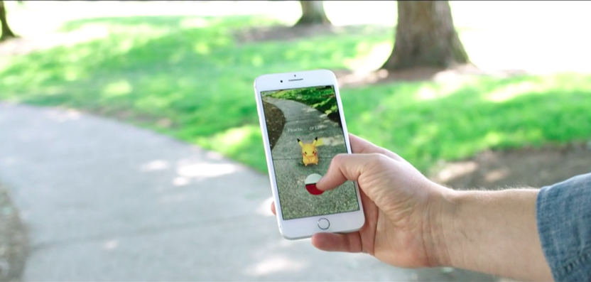 a phone with the game Pokemon Go outdoors in a park