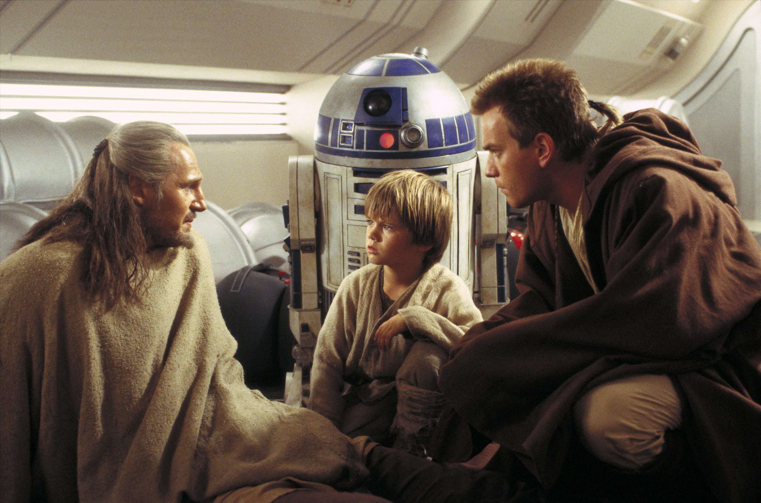 Qui-Gon Jinn introduces young Anakin Skywalker to Obi-Wan, as R2-D2 looks on, in The Phantom Menace.