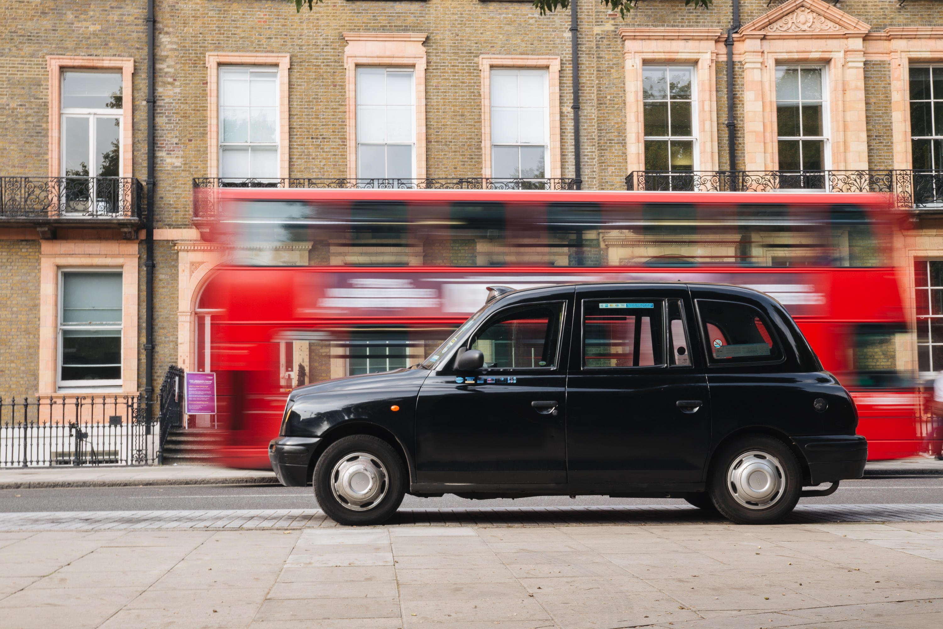 A classic London black cab sits in a parking bay in Russell Square, Central London. A double-decker bus passes behind.