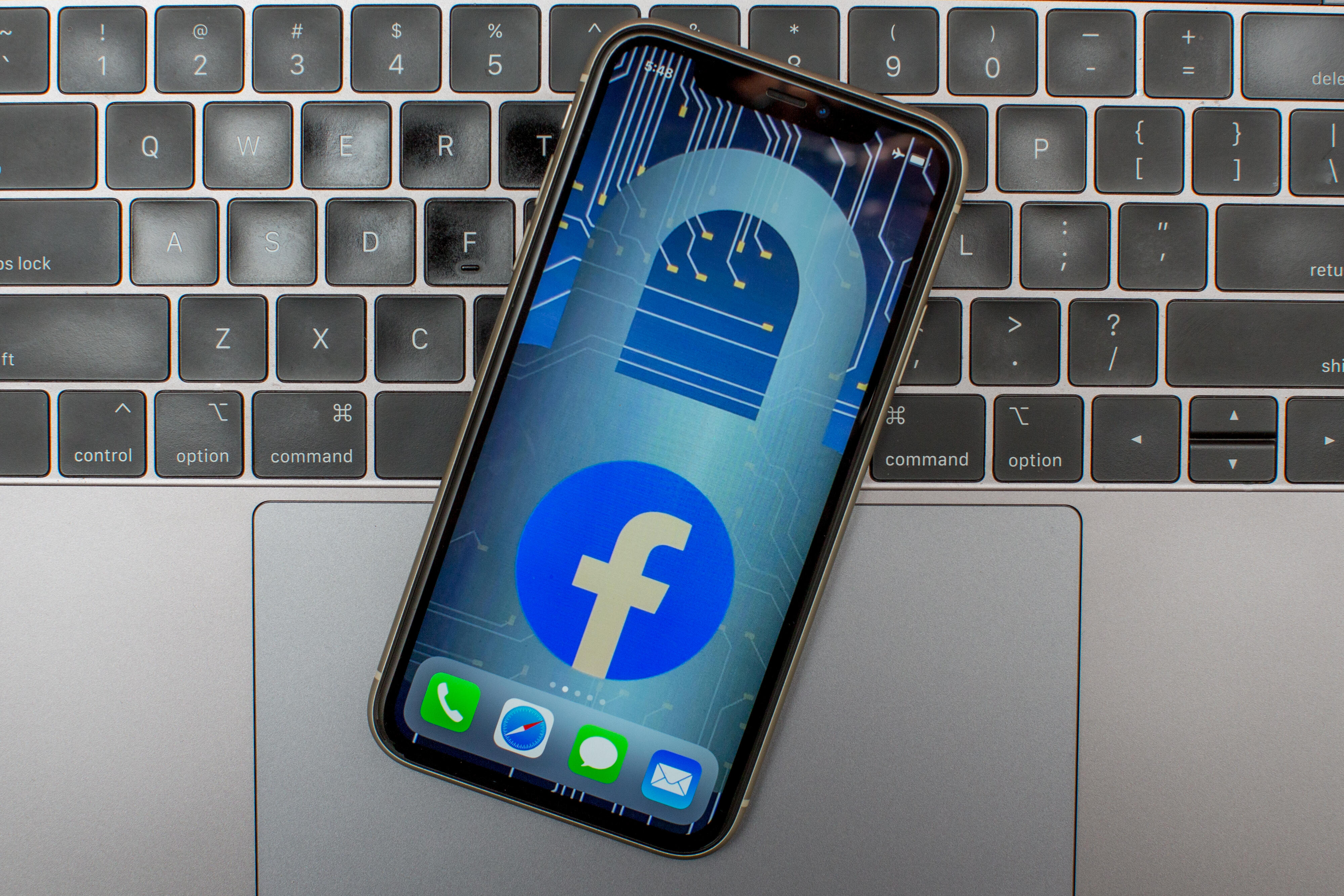 Facebook logo and padlock outline on a phone screen, atop a laptop keyboard