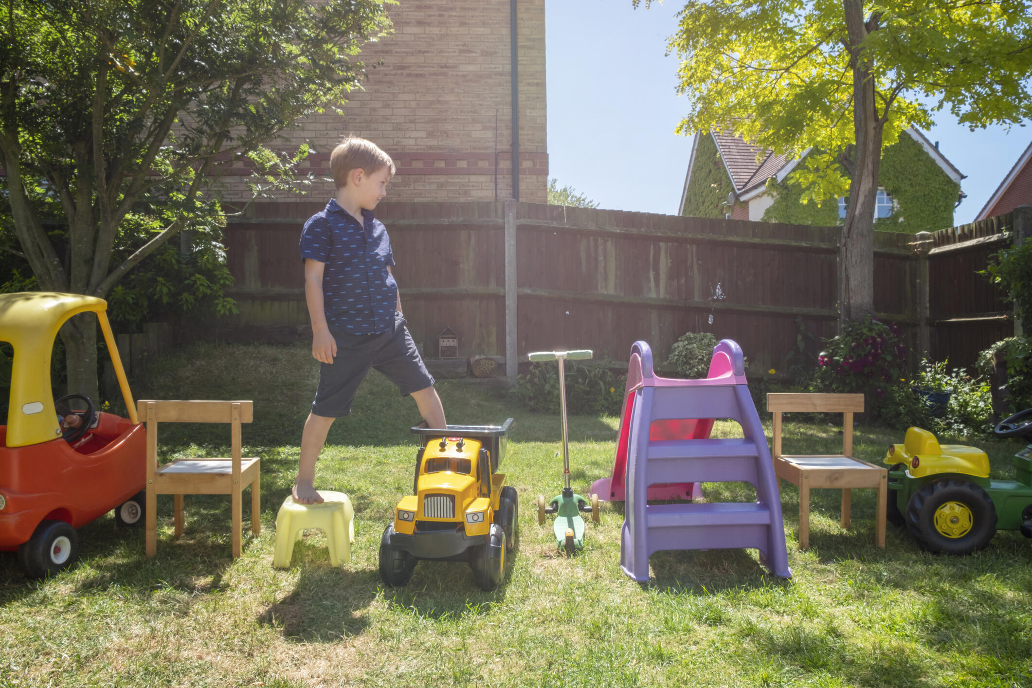 a young boy playing on an obstacle course made of toys in a yard