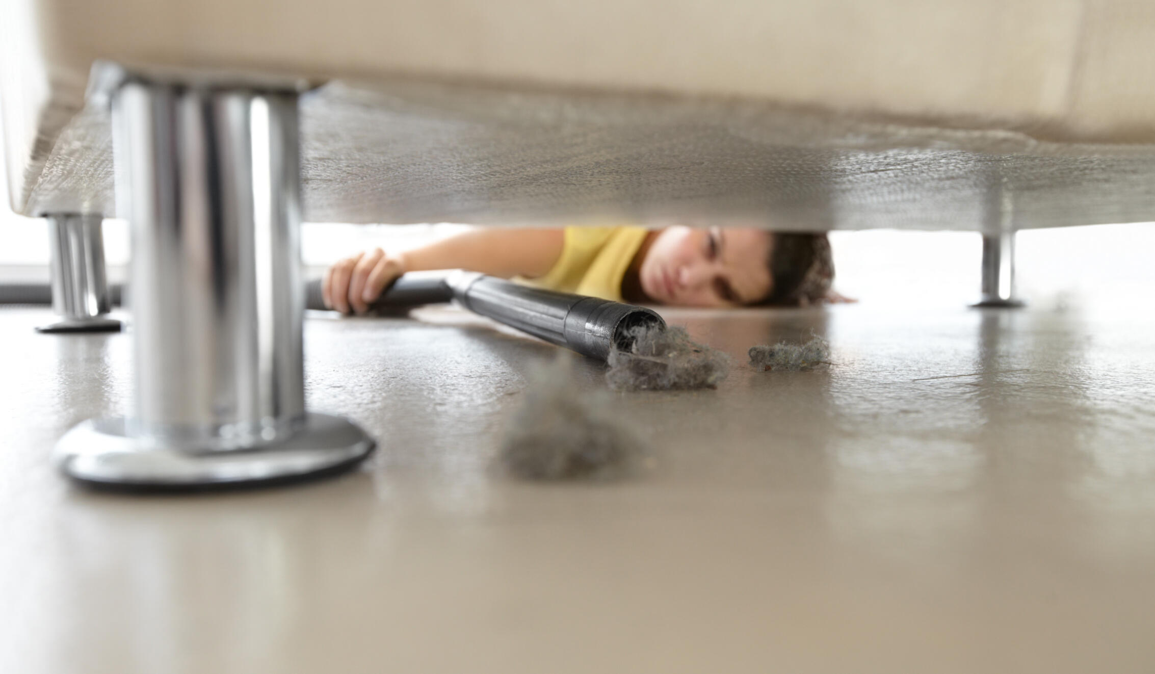 a woman vacuuming up dust from beneath a bed