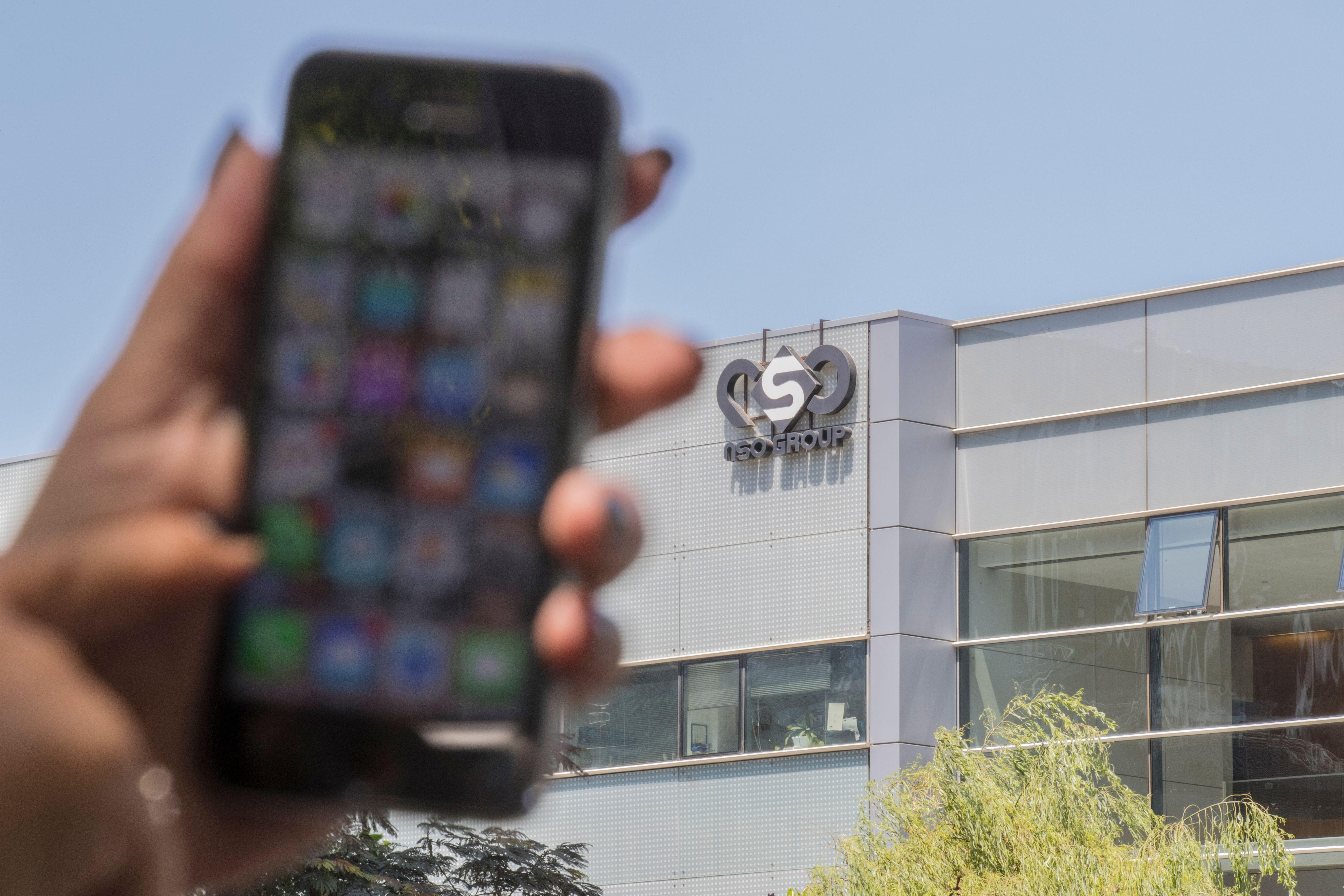 An out-of-focus iPhone is held up in front of NSO Group's headquarters, with the company logo visible on the side of the building.