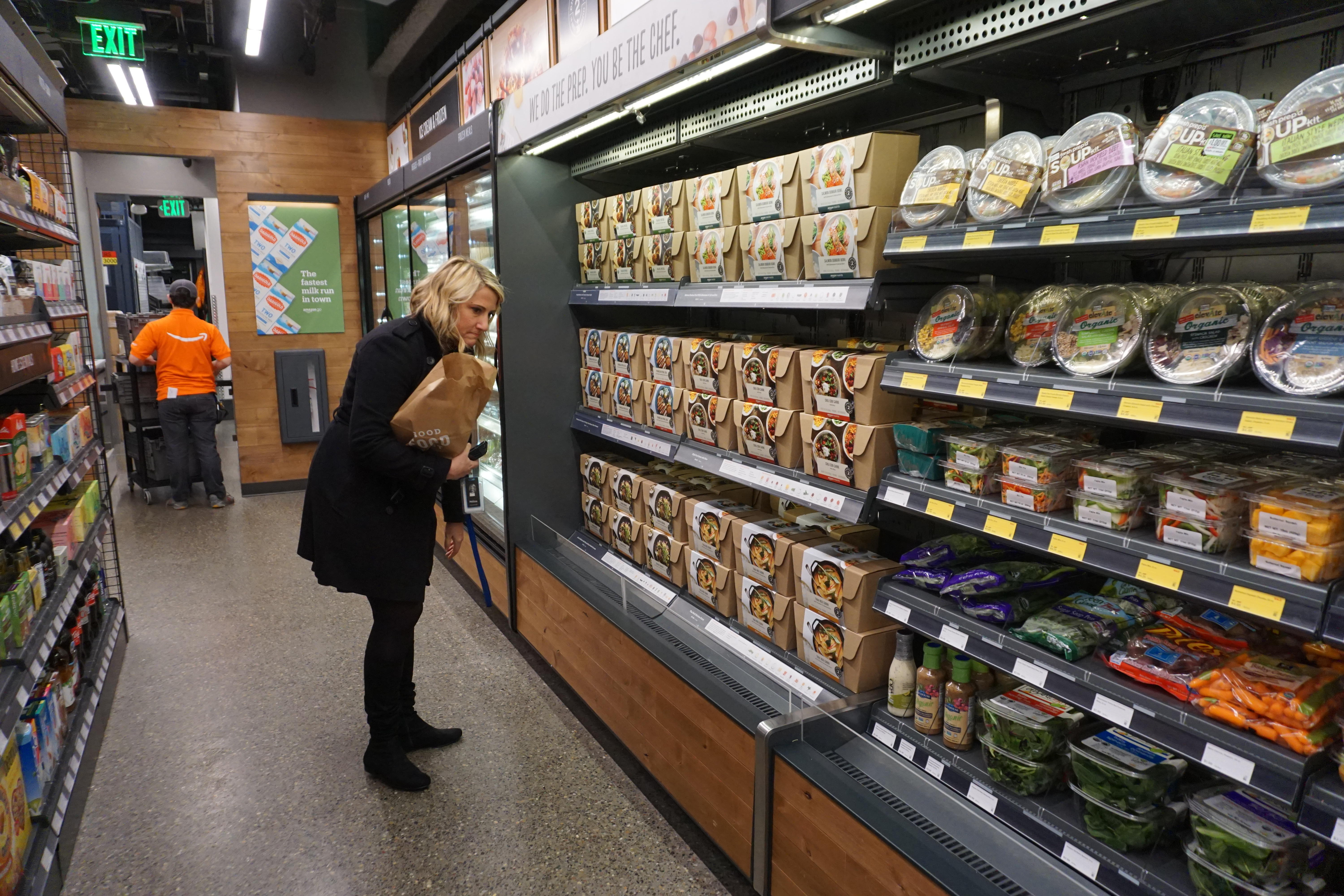 A customer examines Meal Kits in the Amazon Go store.