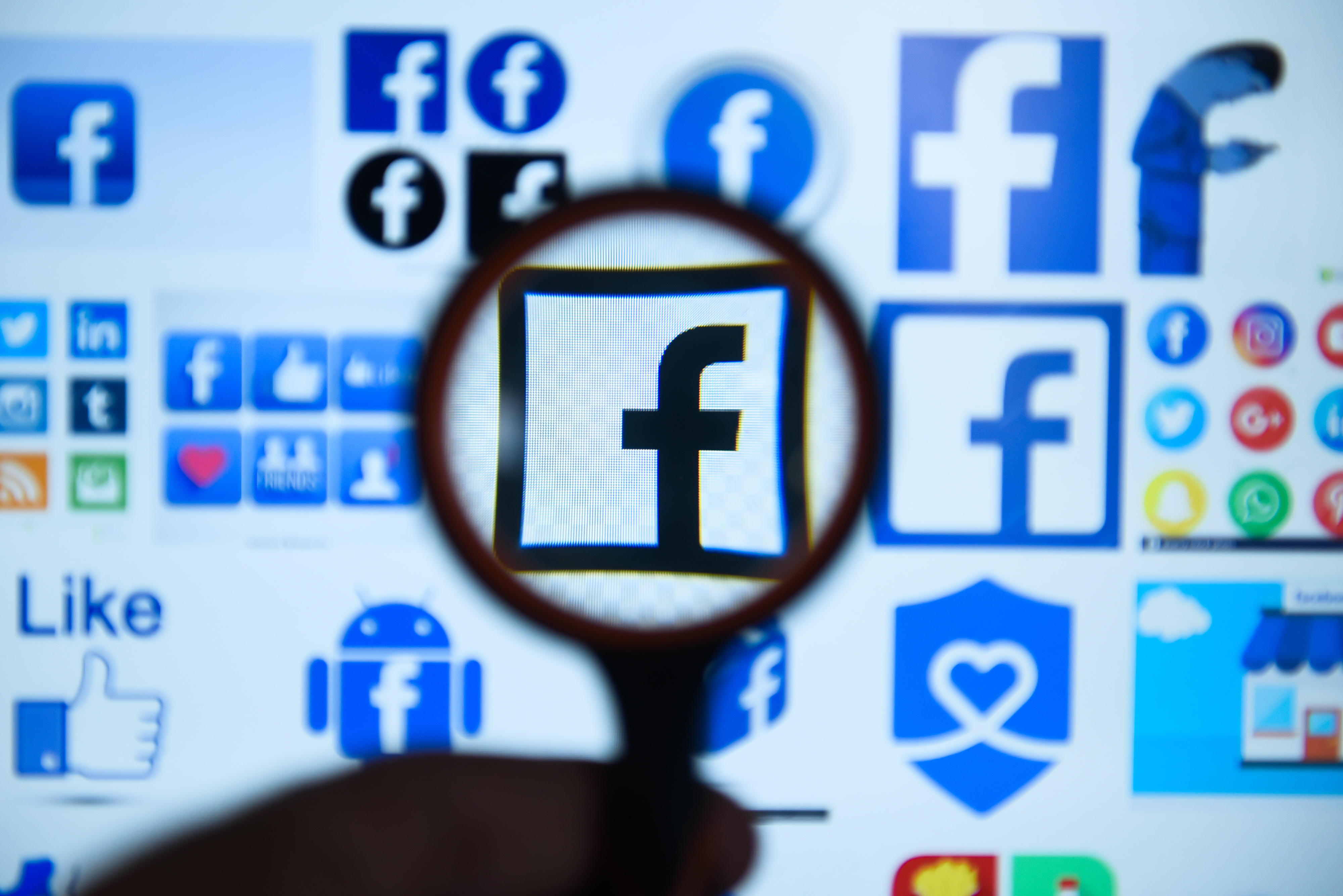 Facebook  logo is seen trough a magnifying glass on a