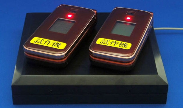 Two phones resting on a charging station receive power wirelessly.