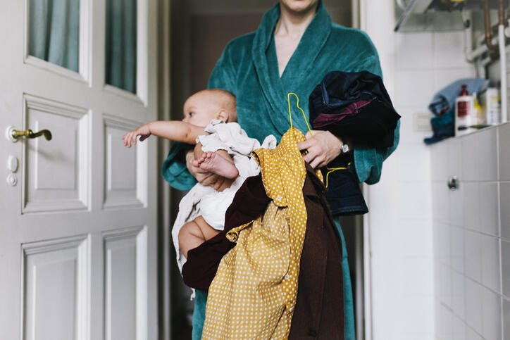 New mom holding baby and clothes