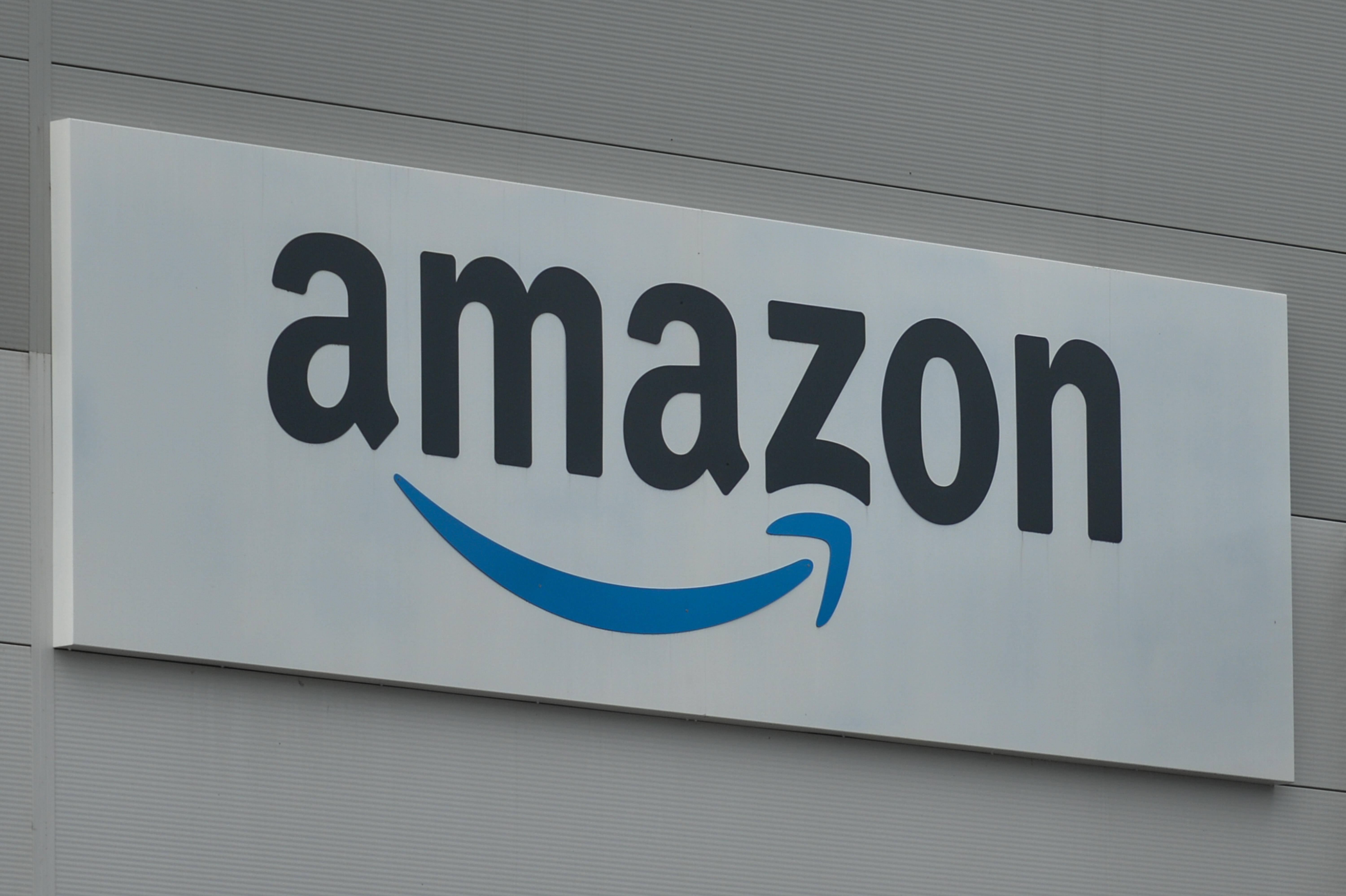 Close-up of an Amazon sign with the company's smile logo on the side of a warehouse.
