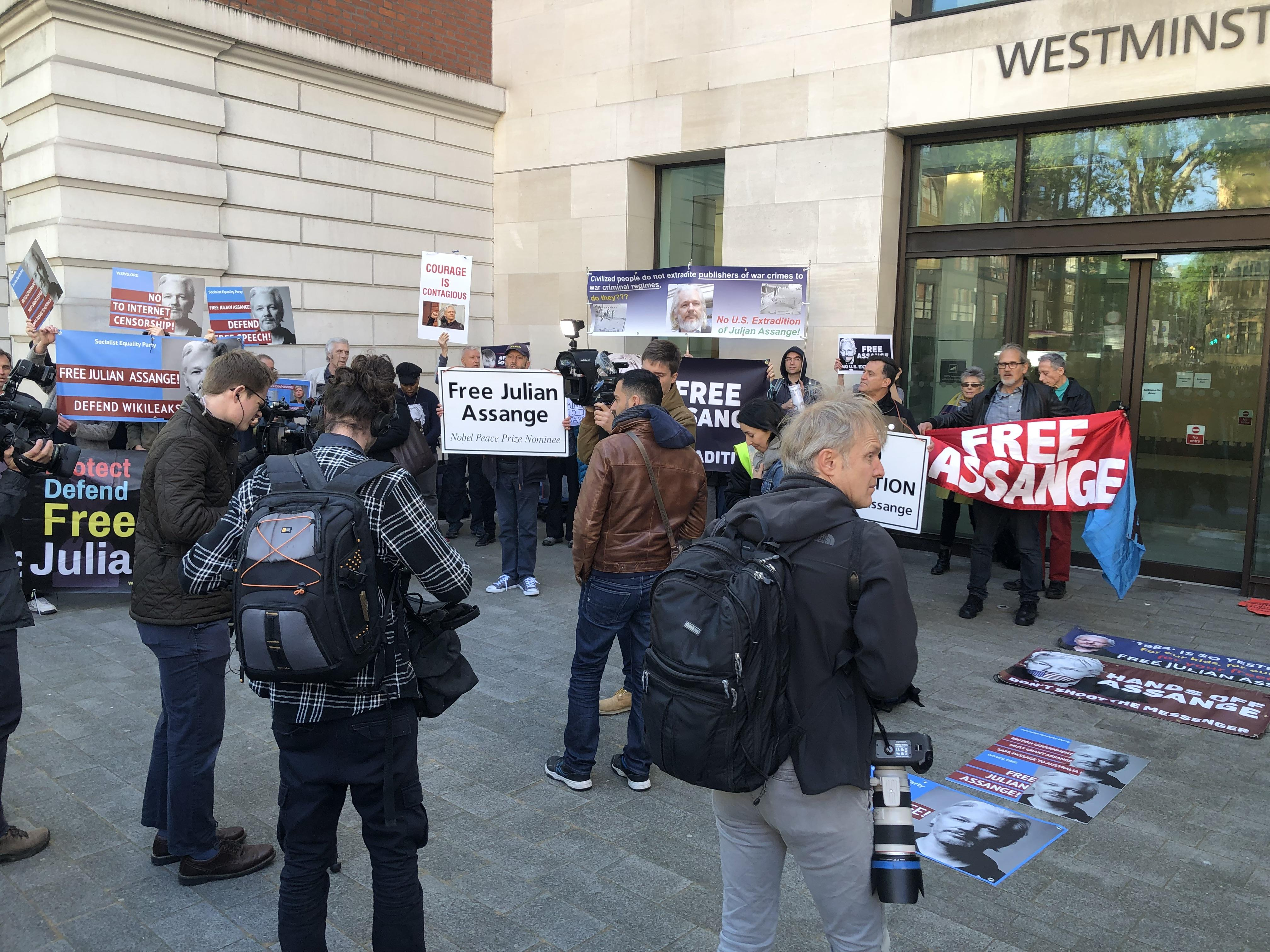 """Protesters outside Westminster Magistrates Court in London, holding signs saying """"Free Julian Assange."""""""