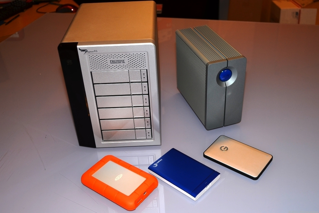 Two multiple-bay external drives next to three portable drives.