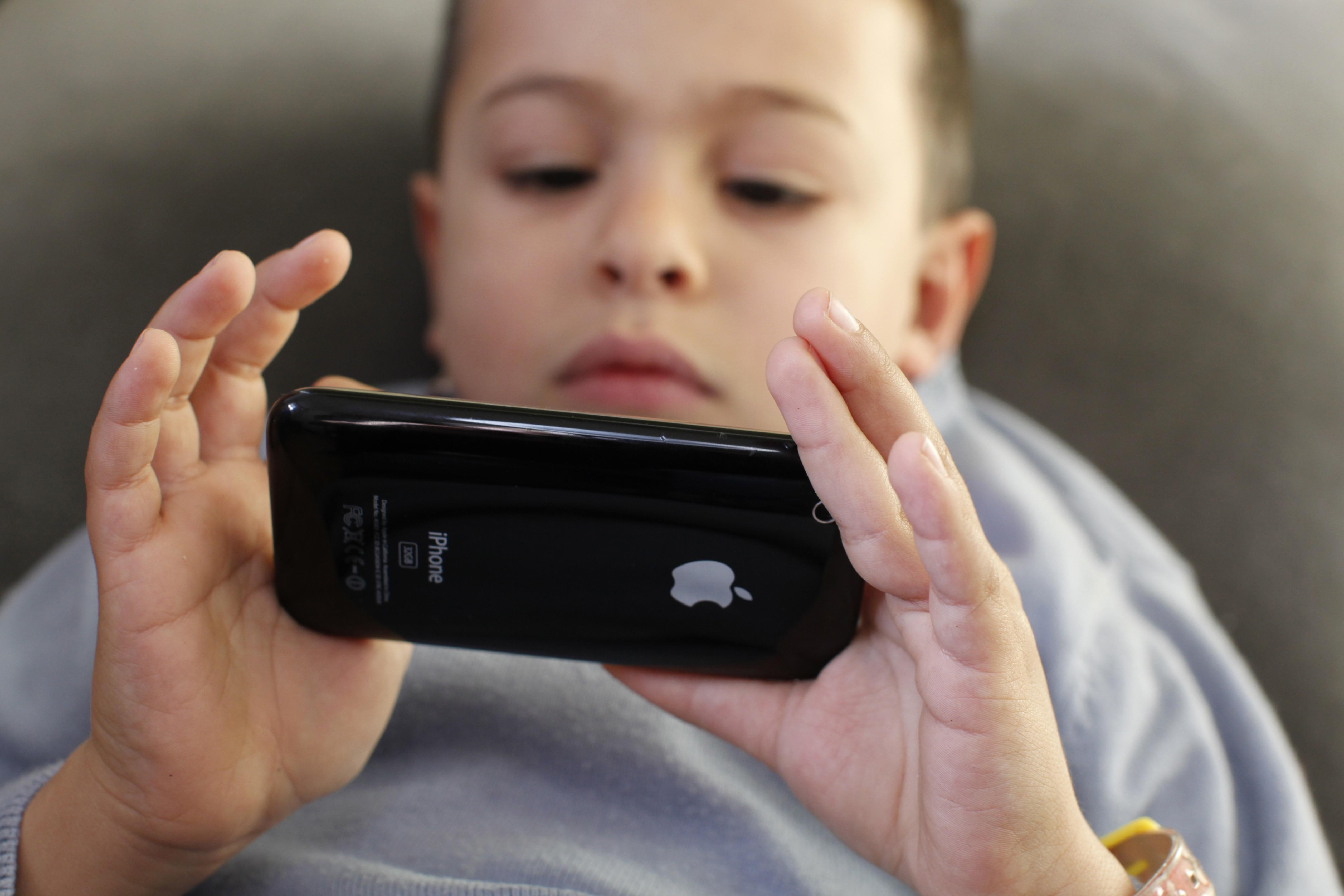 6-year-old boy playing with an Iphone, France