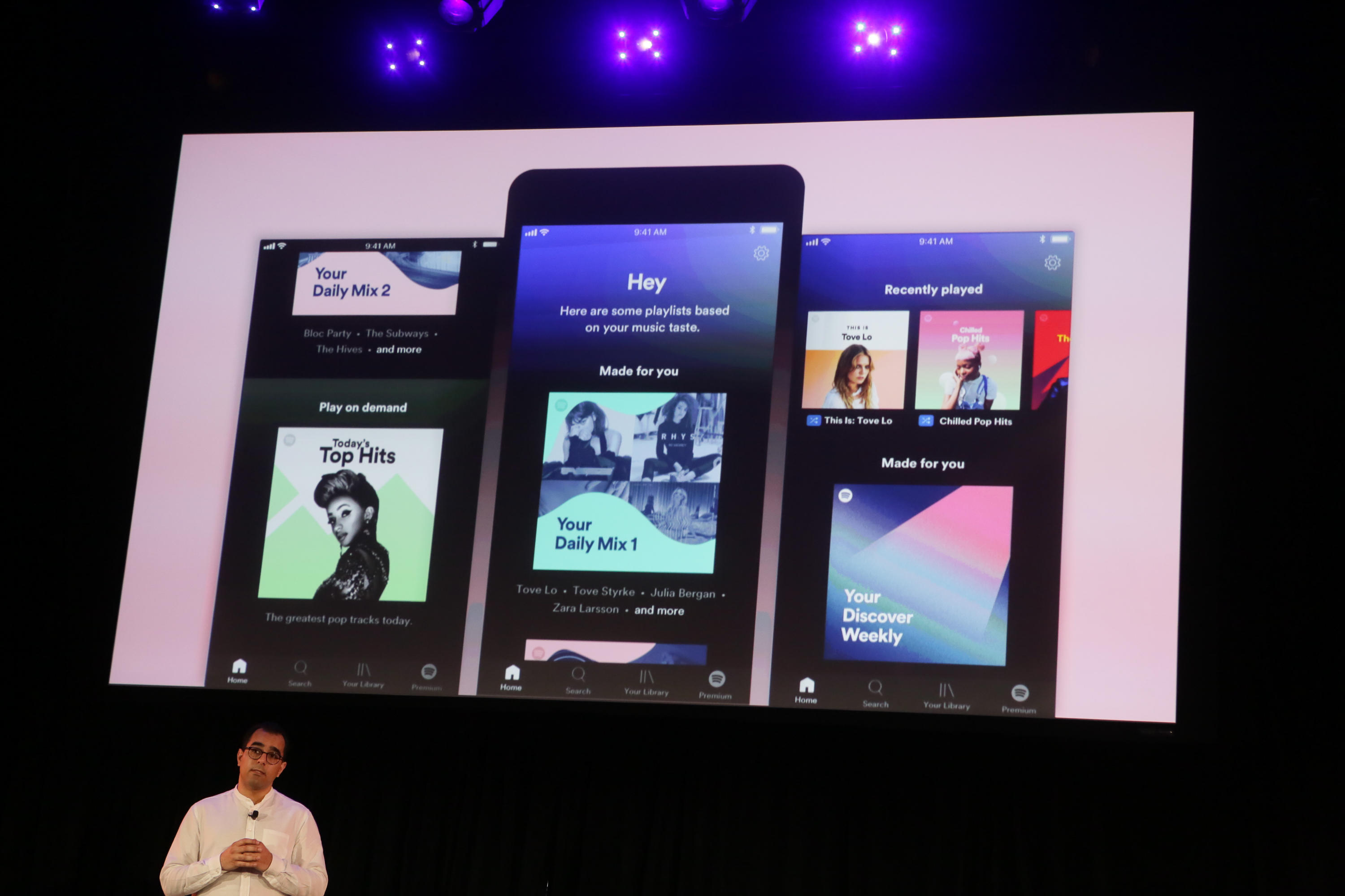 Spotify executive Babar Zafar on stage in front of screenshots of Spotify's new app