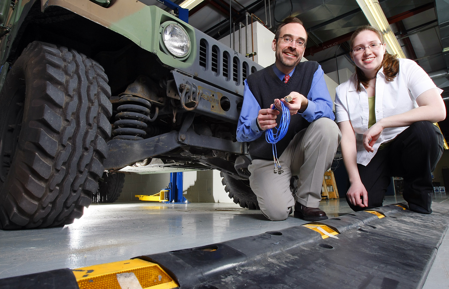 """Douglas Adams, a Purdue associate professor of mechanical engineering, and graduate student Tiffany DiPetta are working to develop a technology that detects damage to critical suspension components in military vehicles simply by driving over a speed bump with """"diagnostic cleat"""" containing sensors."""