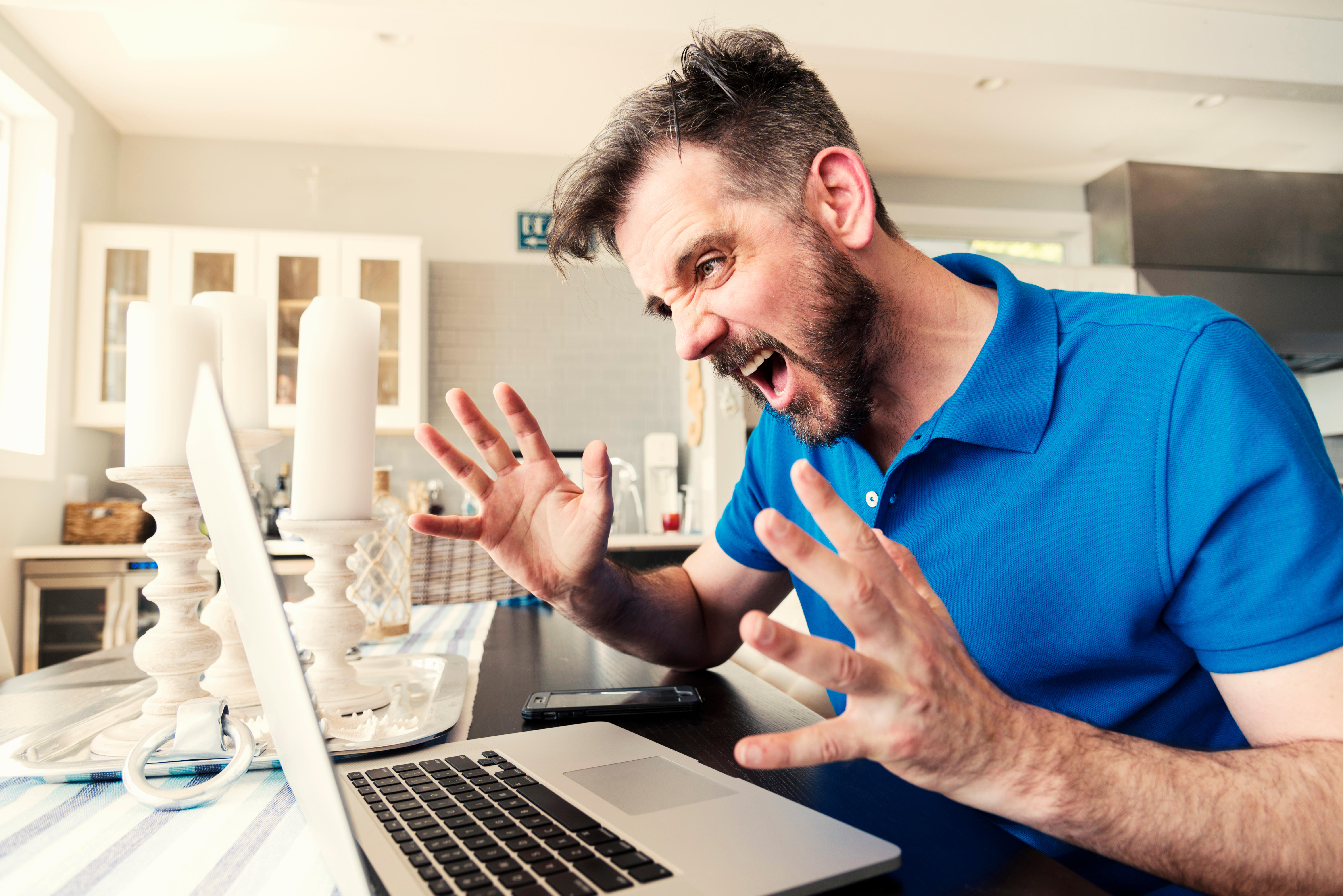 Frustrated Young Man Screaming While Using Laptop