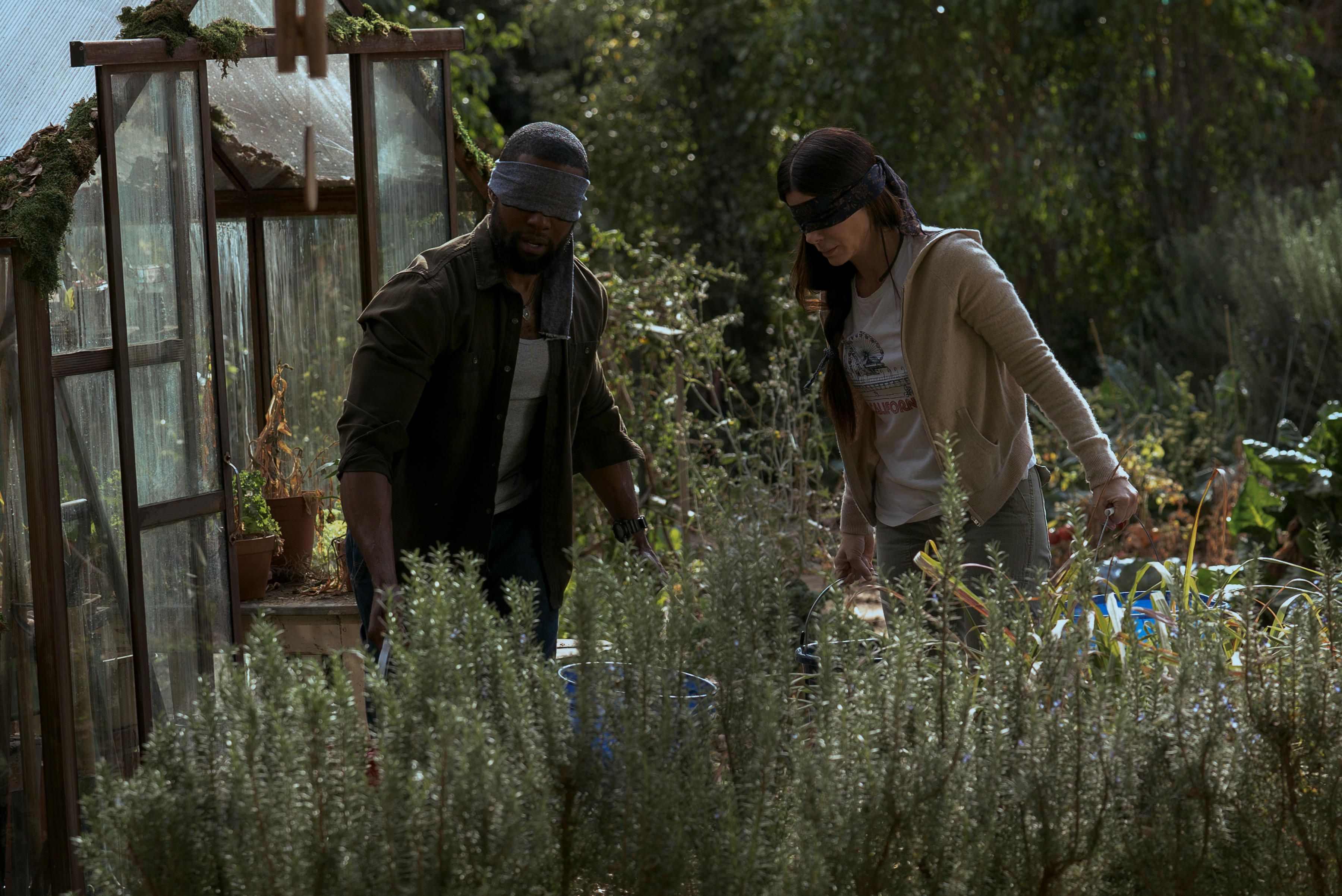 Actors in Bird Box wear blindfolds as they carry buckets in a garden