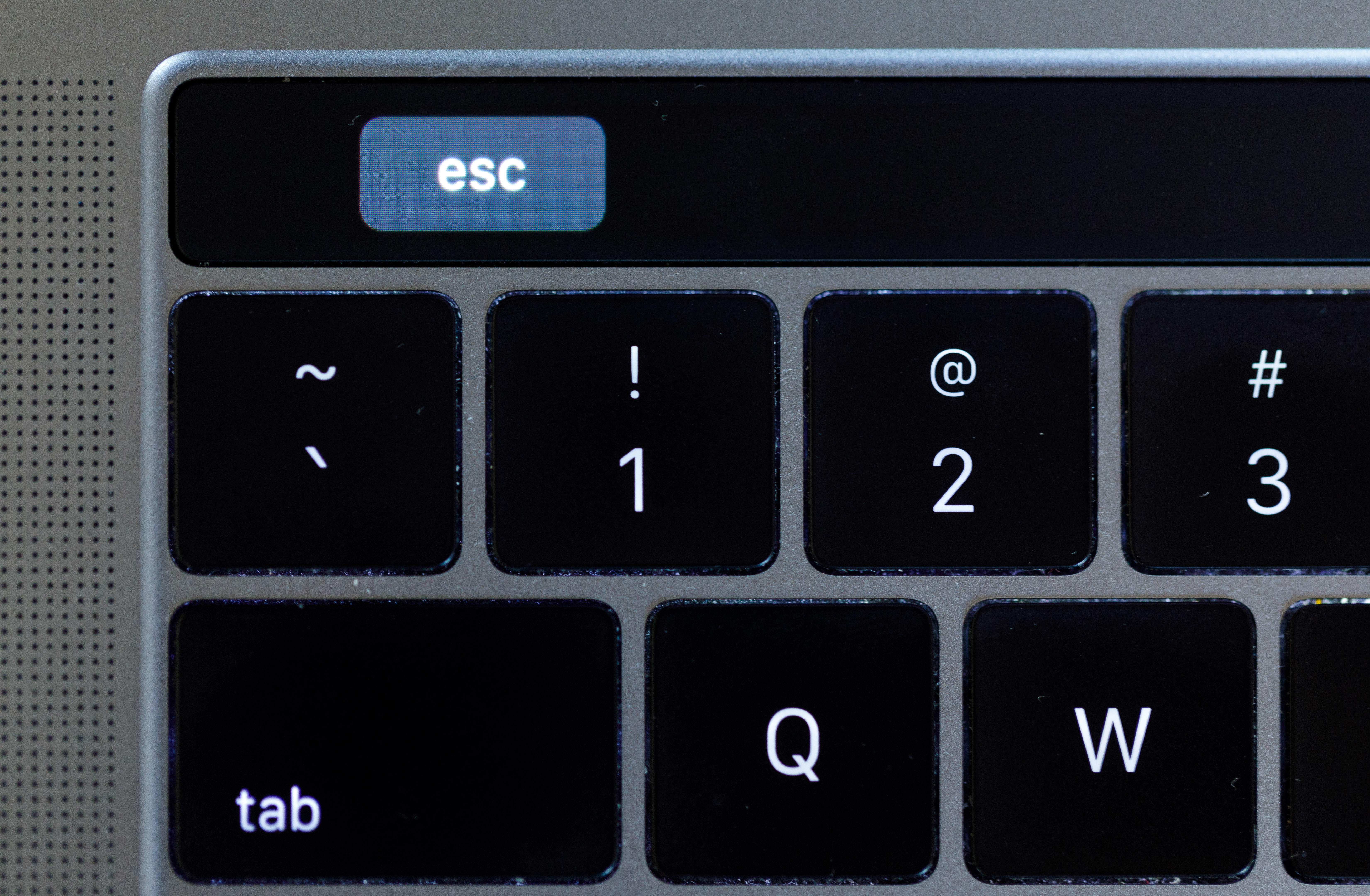 The MacBook Pro Touch Bar's virtual escape key is inset to the right.