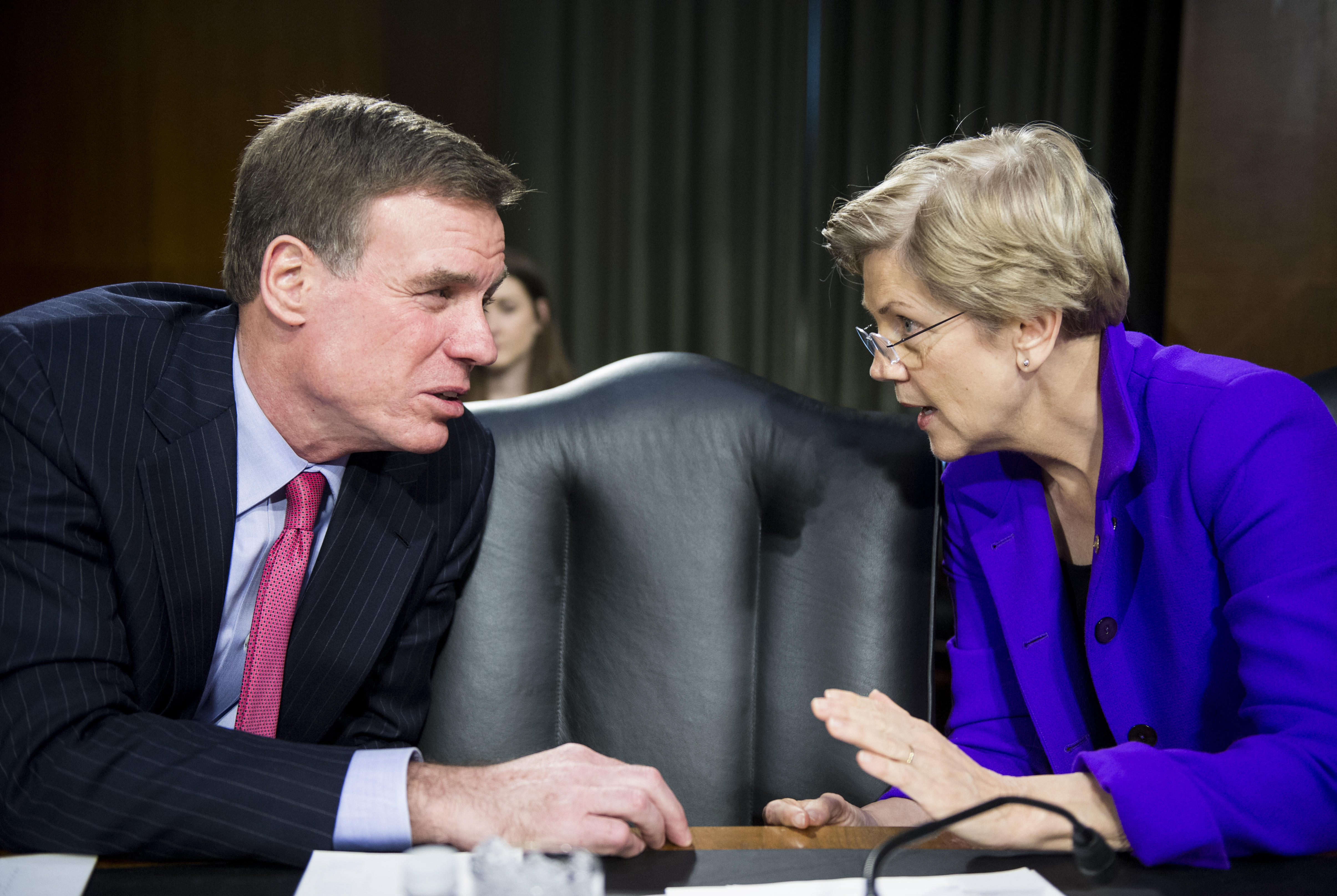 Sen. Mark Warner and Sen. Elizabeth Warren talk with each other in a Senate meeting room before the start of a hearing in 2015.