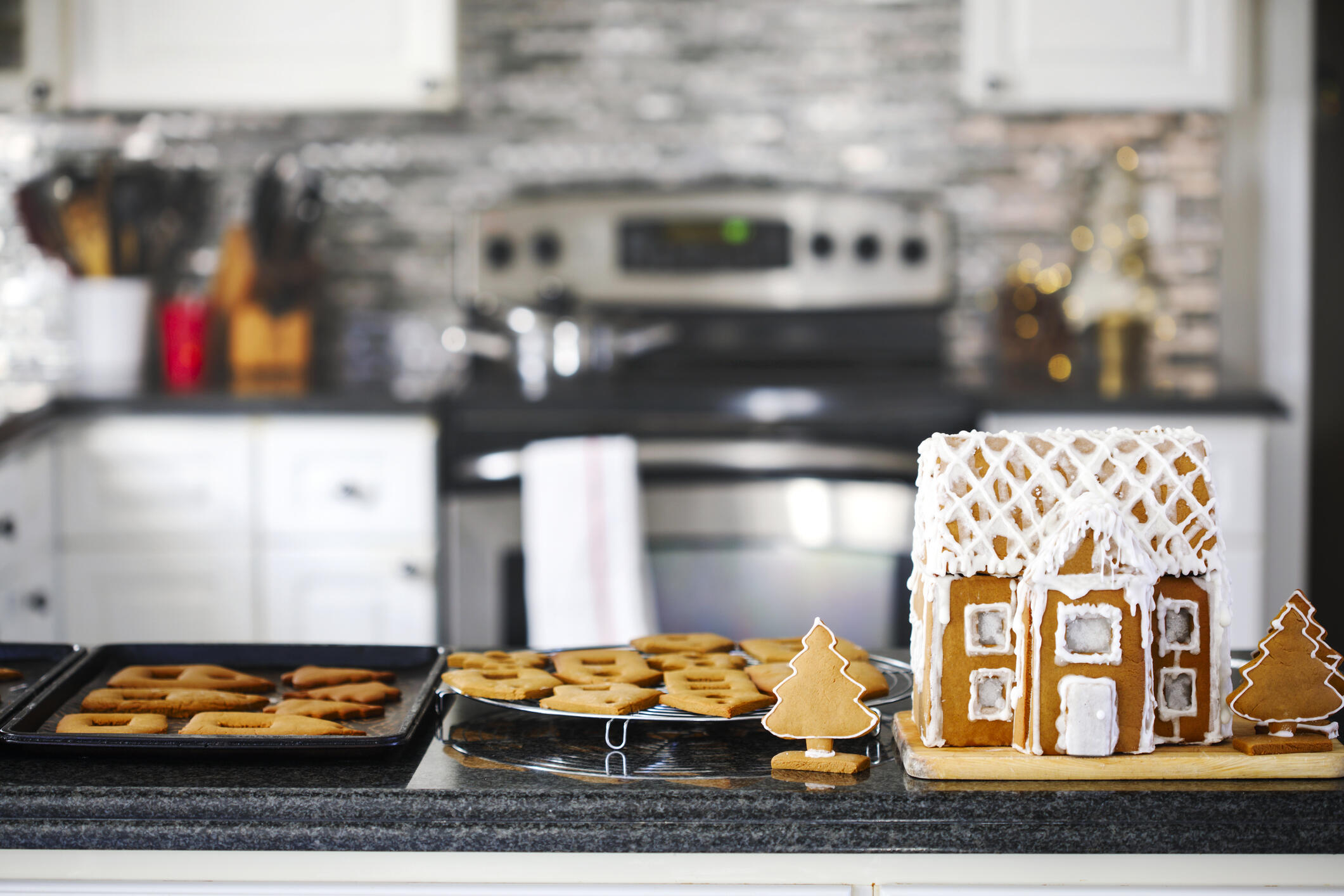 Gingerbread house and cookies on a kitchen counter.