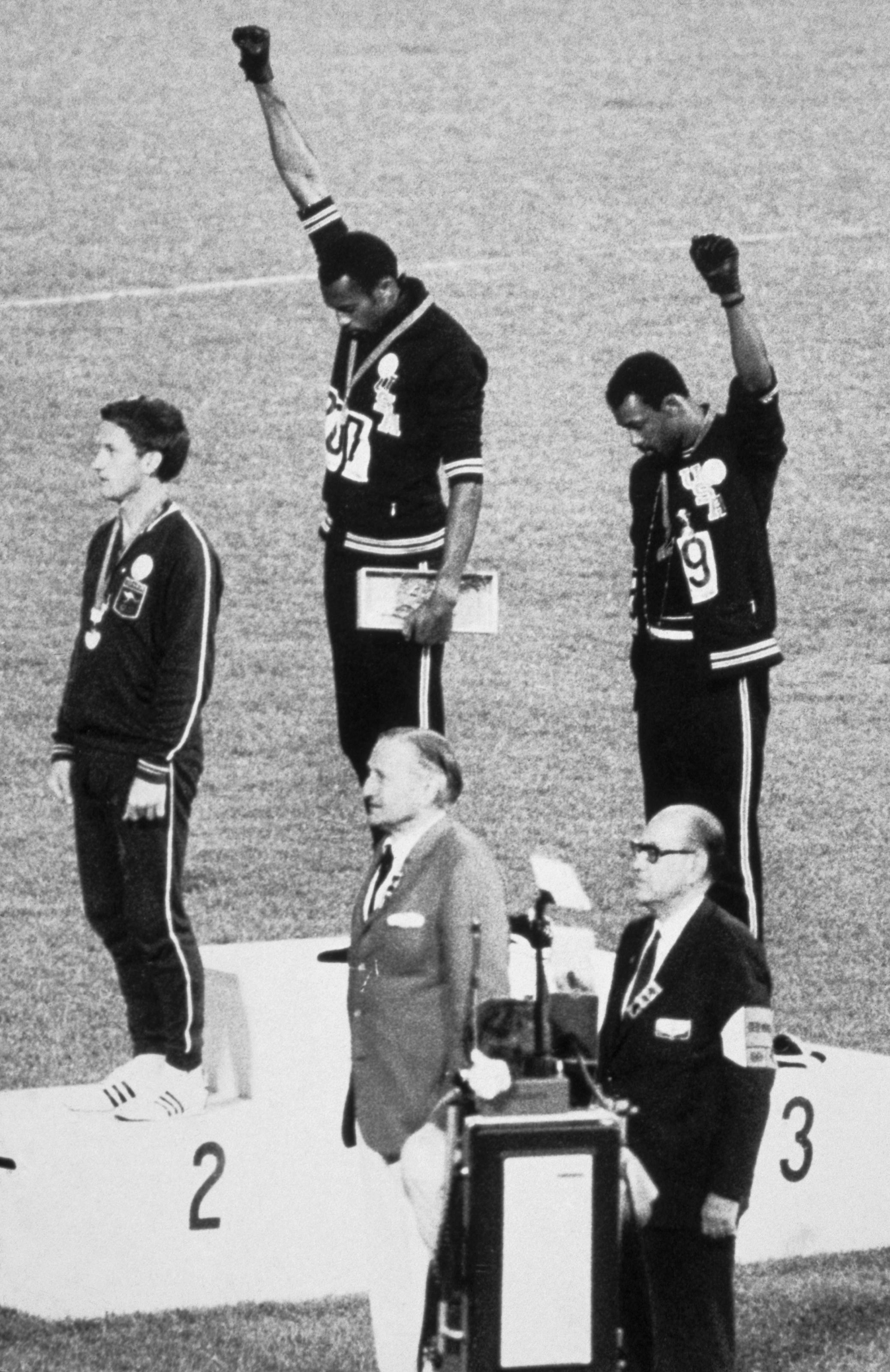 American sprinters Tommie Smith and John Carlos raise their fists as the national anthem plays at the 1968 Olympics.