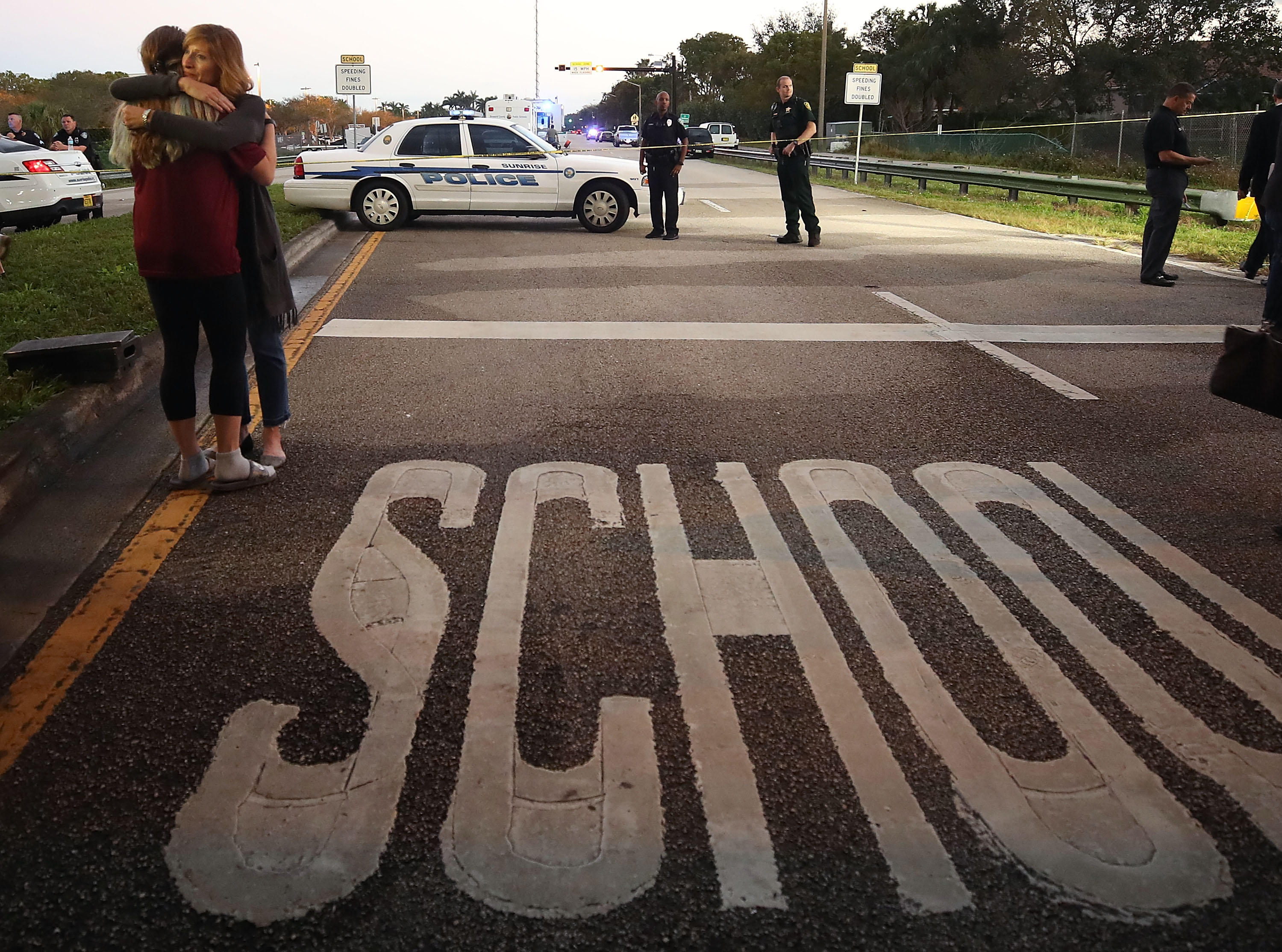 Two women hug at a police checkpoint near Marjory Stoneman Douglas High School, where 17 people were killed by a gunman Wednesday.