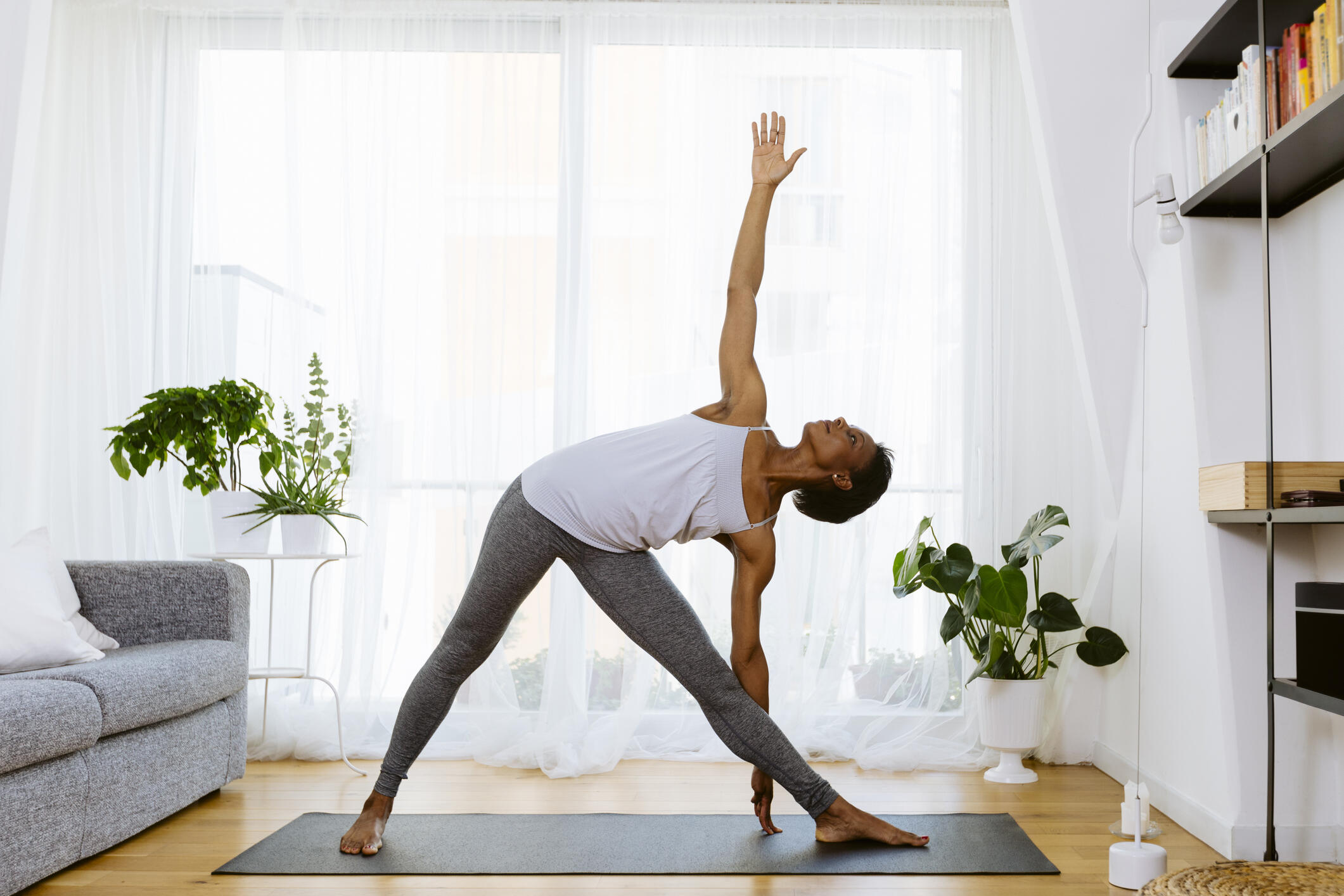 A woman doing yoga in the living room gentle exercise
