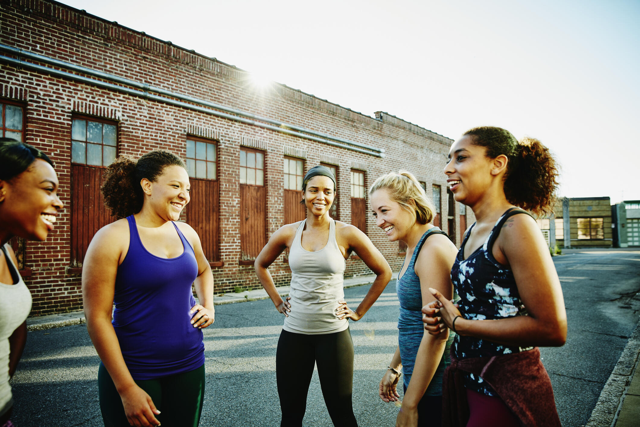 fitness community young women laughing after a workout outside