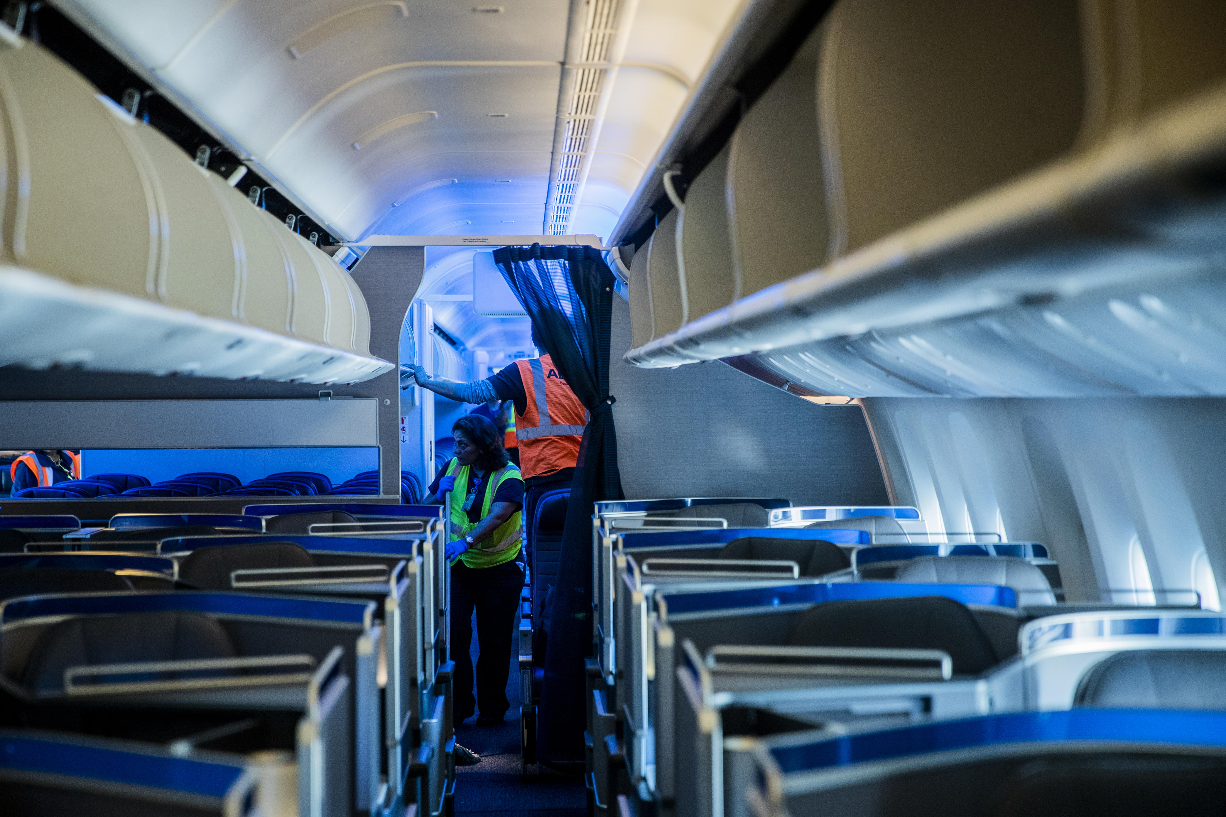 In the cabin of a Boeing 777, cleaning crews vacuum the floor and check the overhead bins for left items.