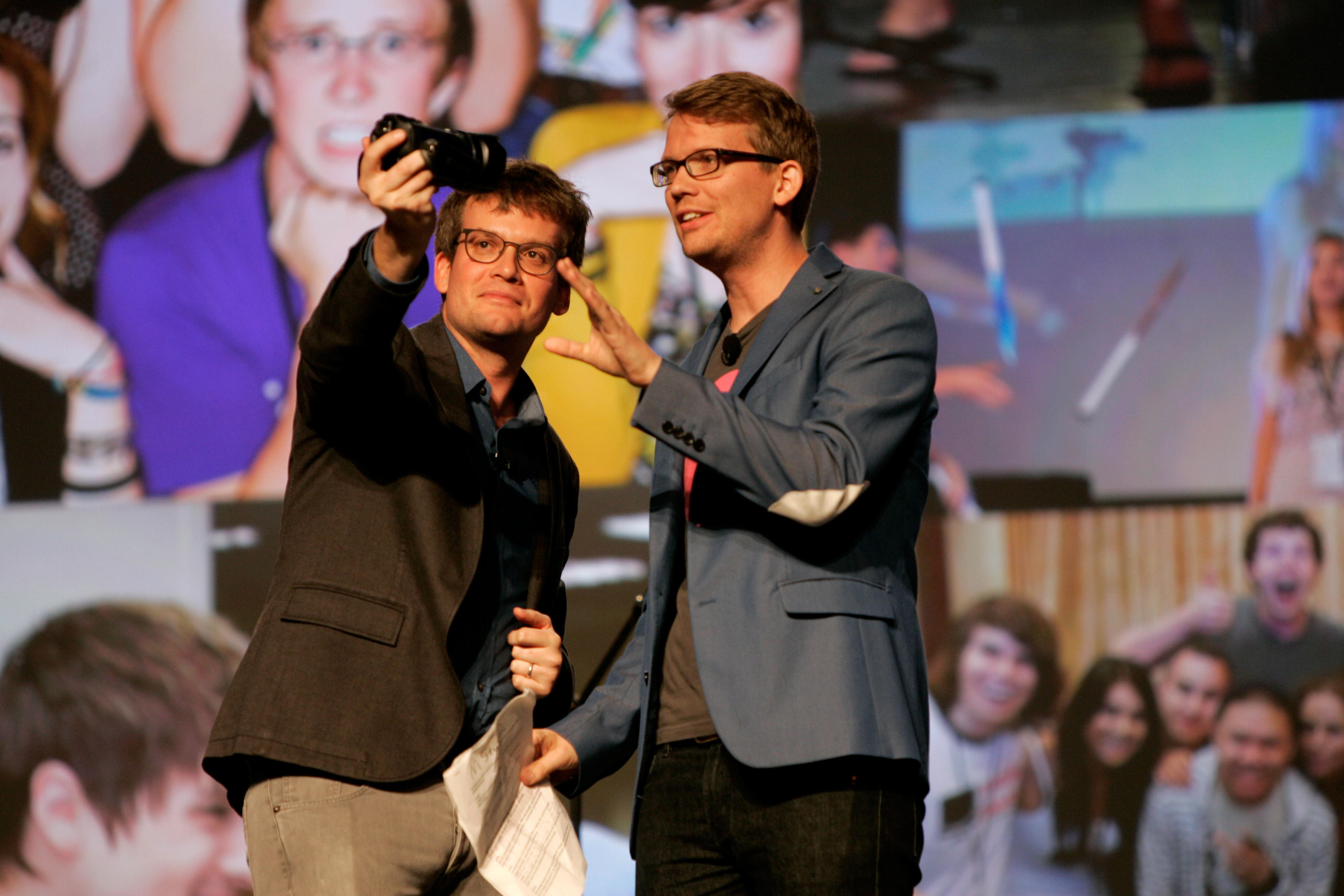 Hank Green and John Green stand on stage, shooting themselves with a video camera