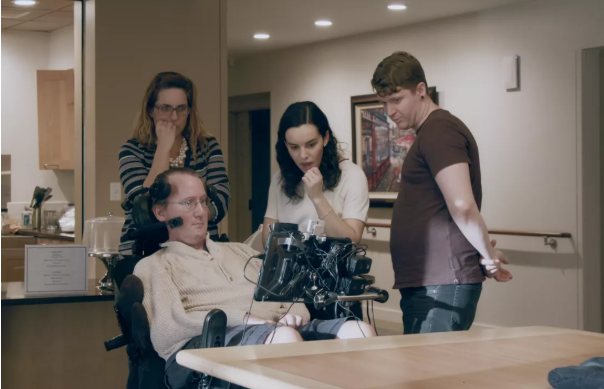 Photo of four people looking at Google AI technology designed to help people with speech impairments more easily communicate.