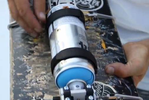 Paint can mounted to skateboard
