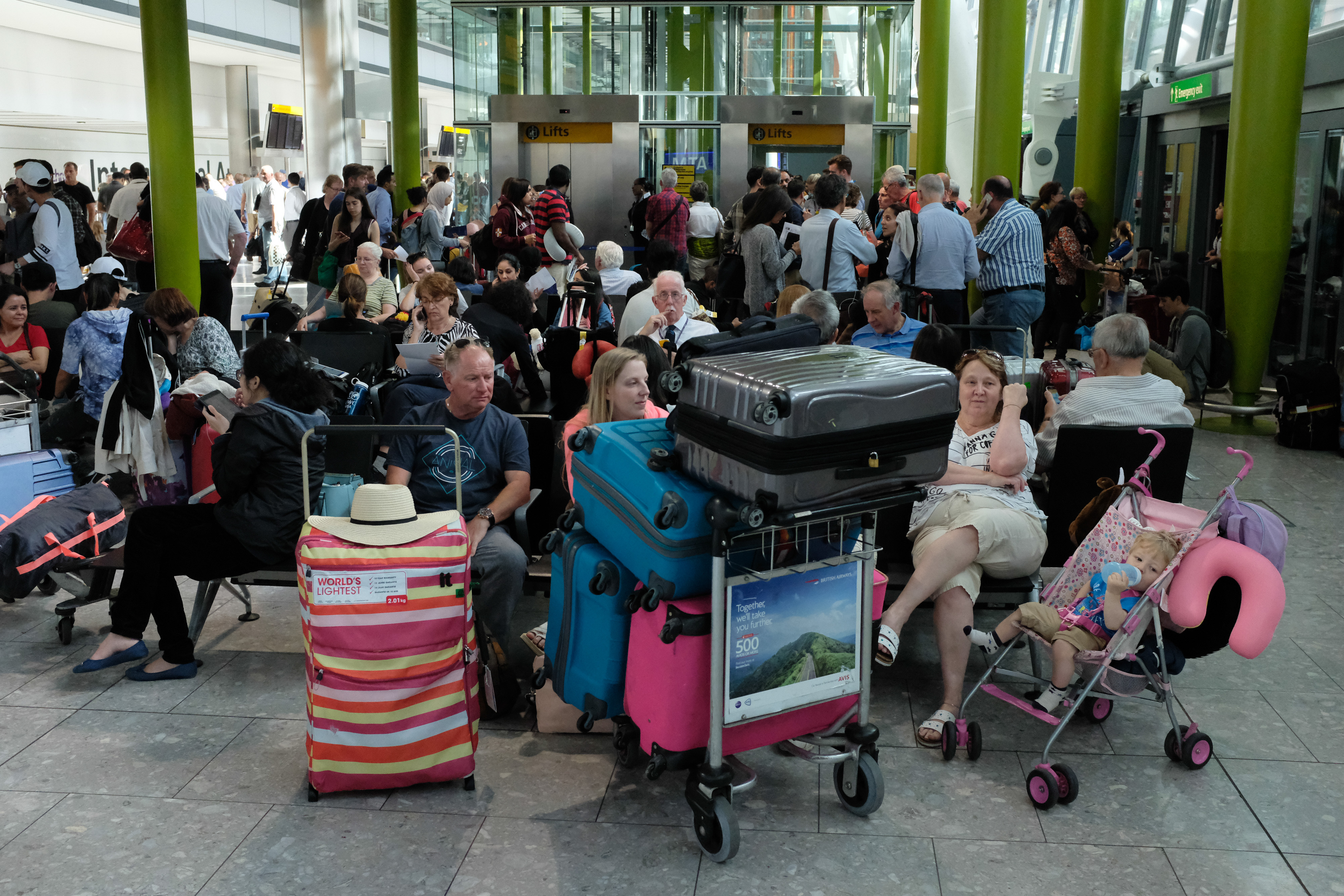 Travelers stranded at Heathrow Airport's Terminal 5 after British Airways canceled flights due to an IT systems failure.