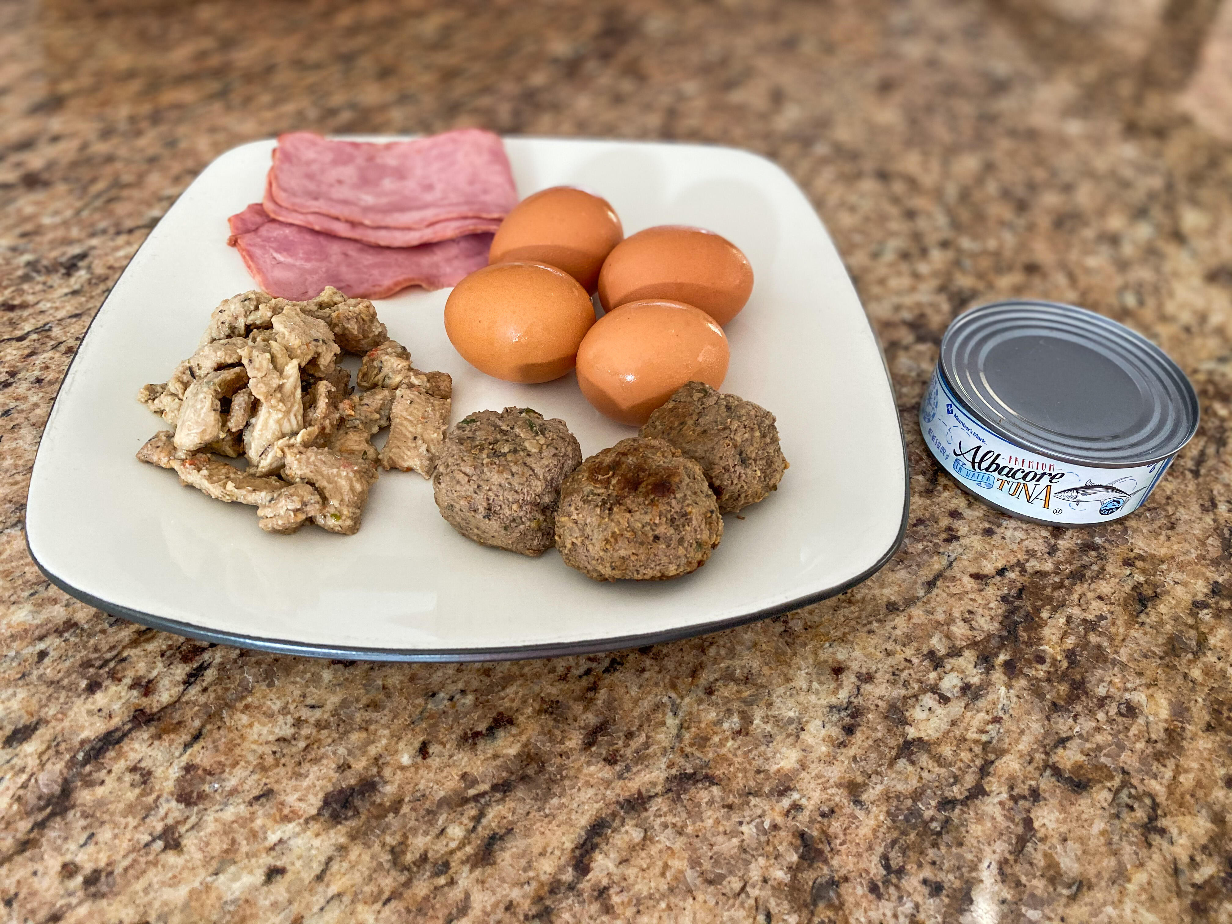 A spread of food containing turkey, ham, eggs, tuna, and beef depicting 100 grams of protein