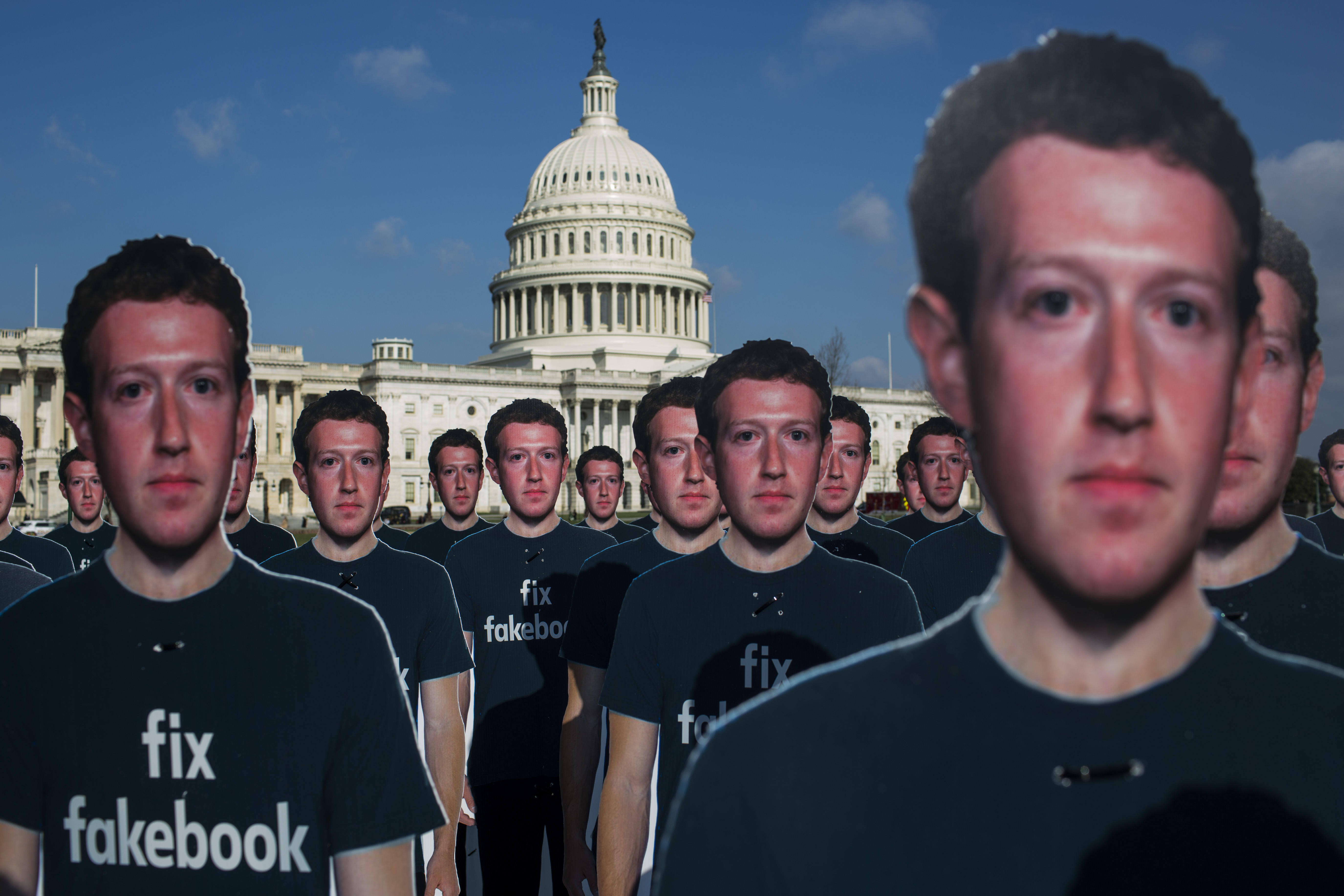 Cutouts of Facebook CEO Mark Zuckerberg in front of the US Capitol building.