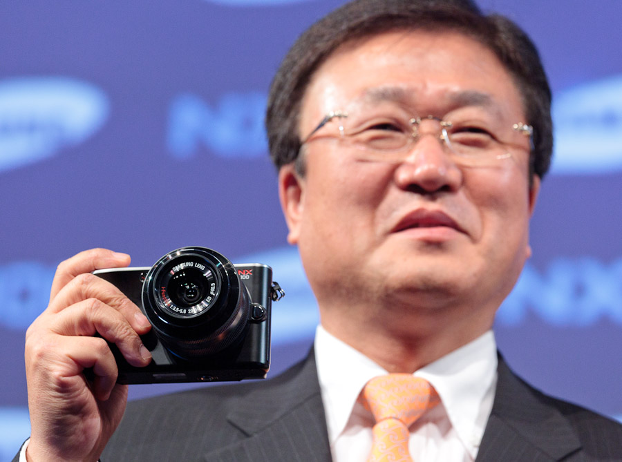 Sangjin Park, president of Samsung's digital imaging division, holds the NX100 at a press conference at the Photokina show in Cologne, Germany.