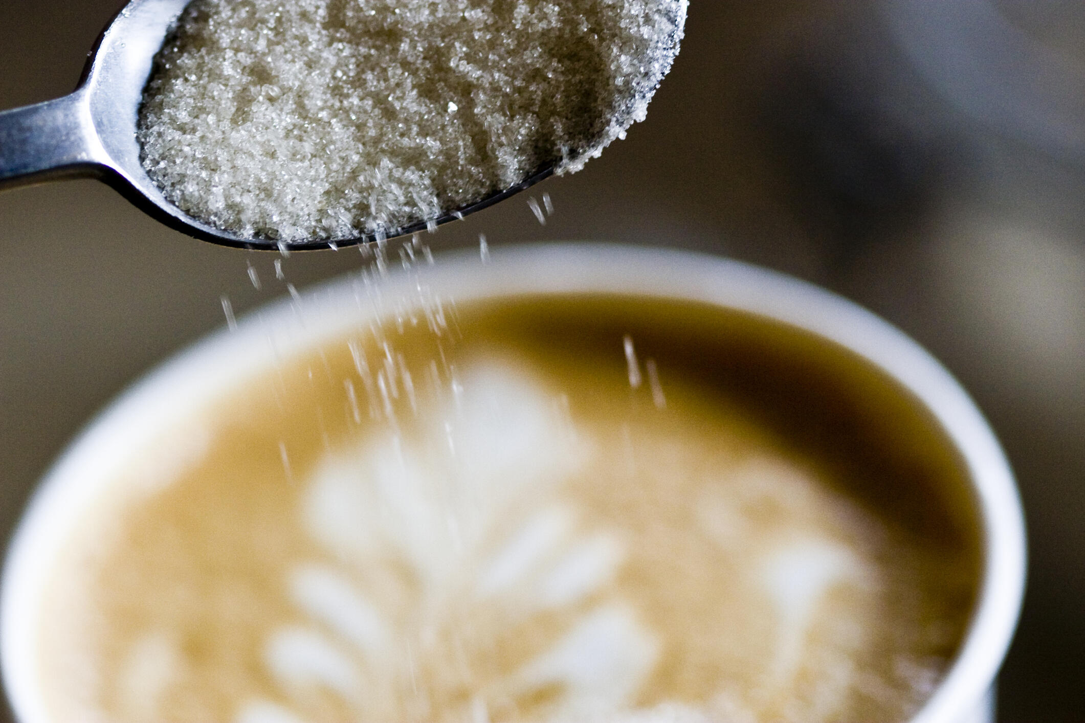 A spoon of sugar being poured into a latte. Latte has a pattern with milk and espresso.