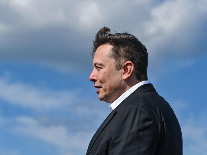 Elon Musk in profile against a blue sky and clouds. Wind stirs his hair.
