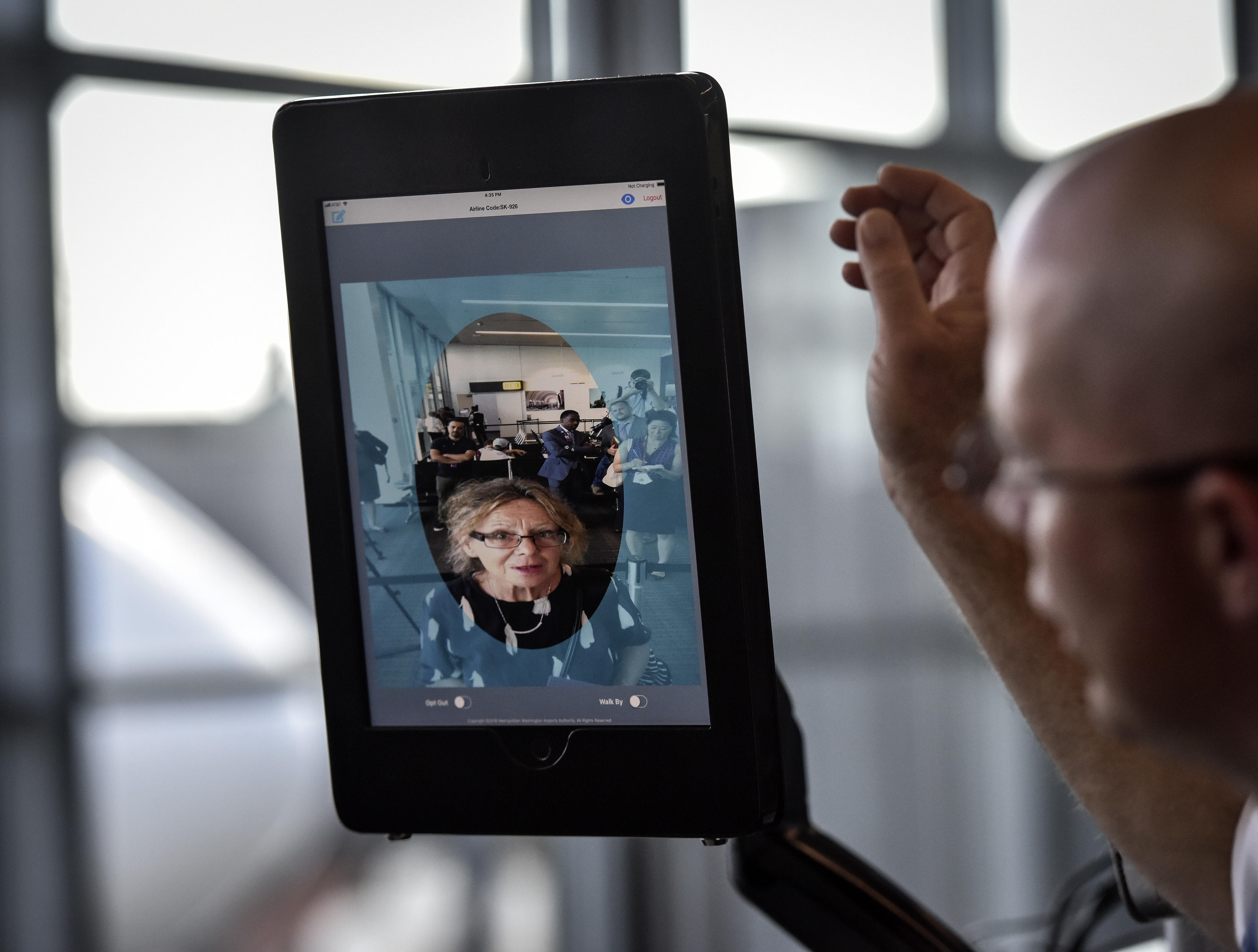 A woman's face appears on a screen while an airport official stands close by.