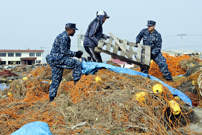 Japanese man removes debris from Misawa fishing port